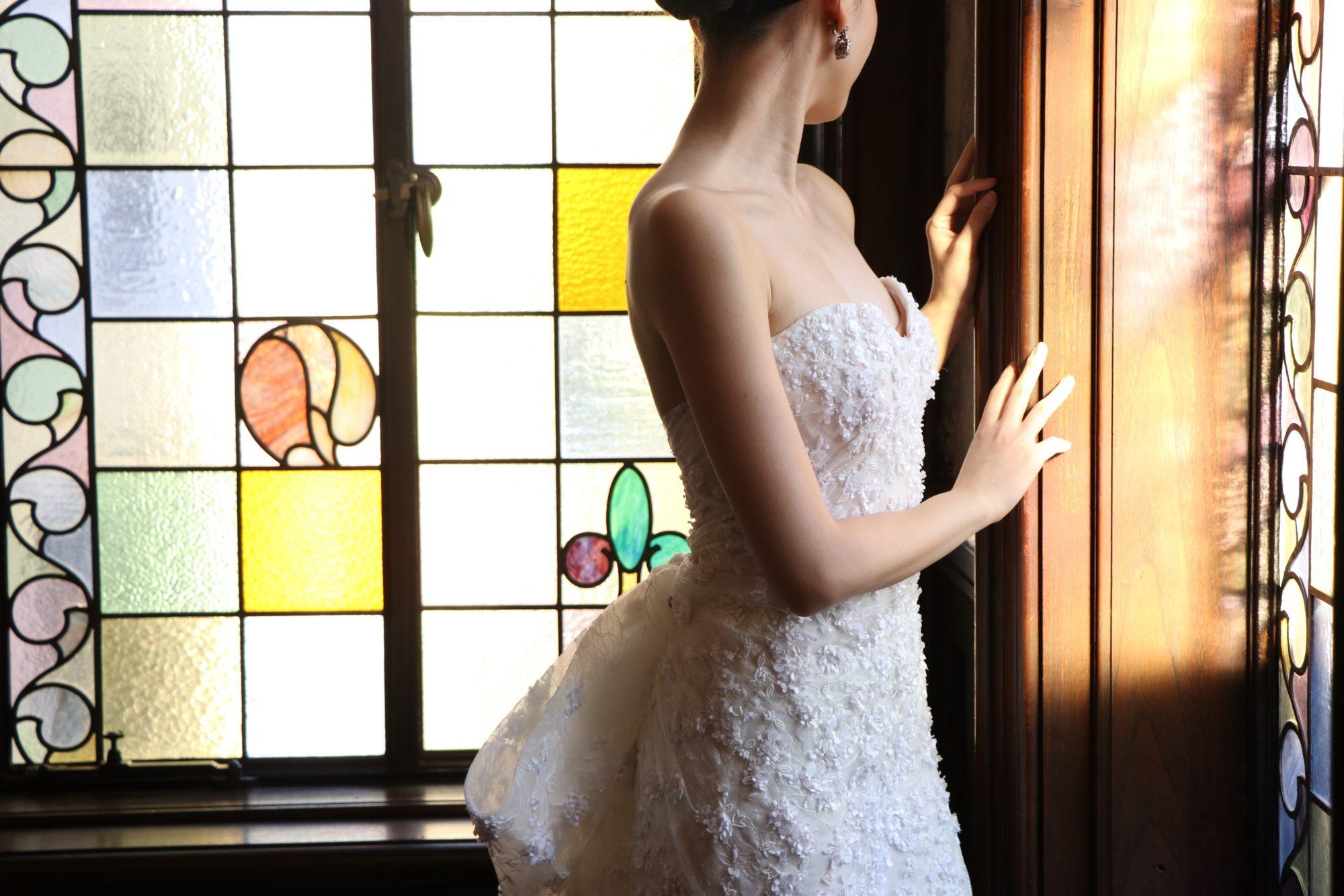 ステンドグラスに映えるビーディングが美しい細身のウエディングドレス