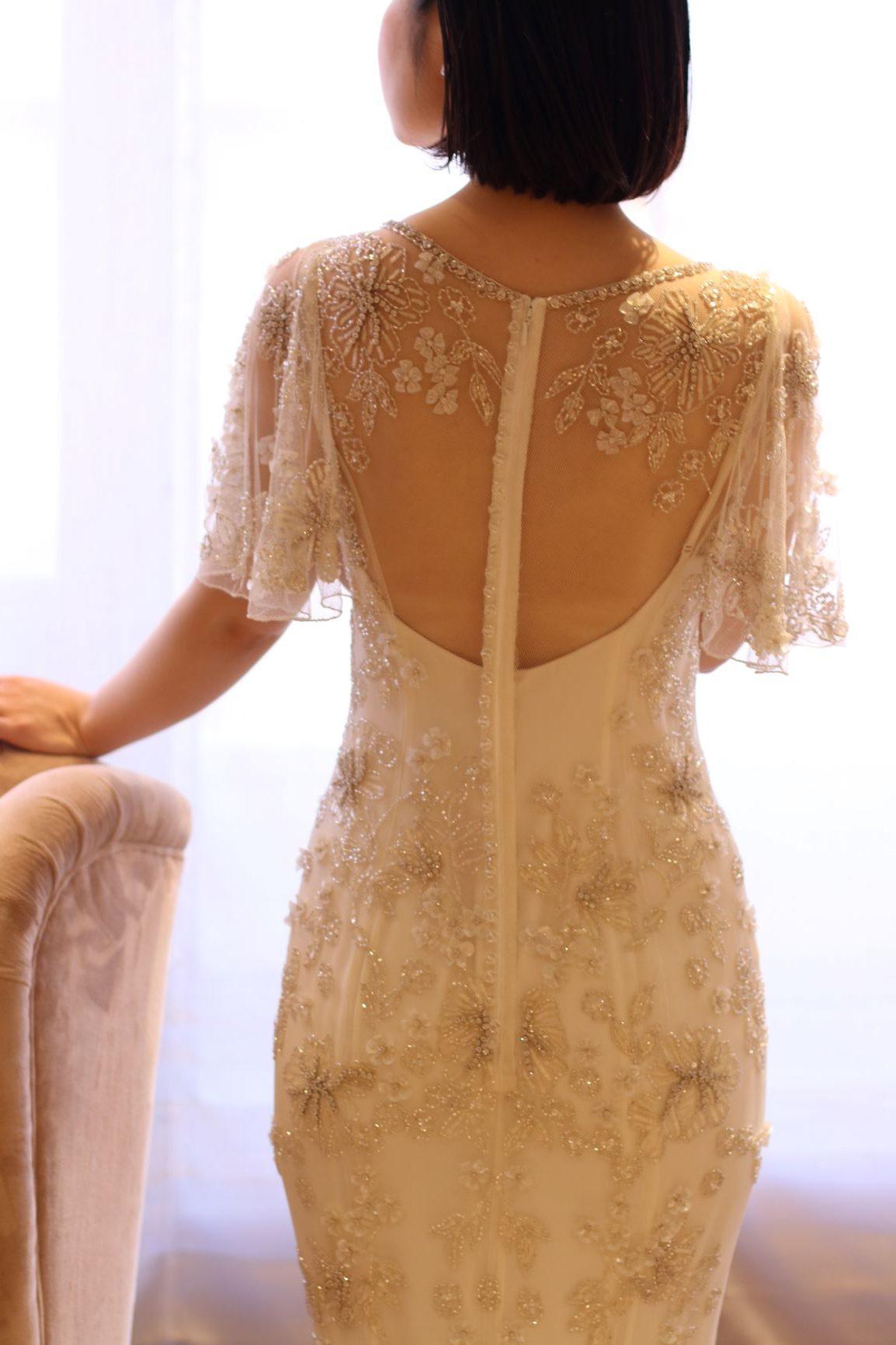 大きく空いたお背中に浮かび上がるようなフラワーモチーフのビーディングが、ゲストを魅了する圧巻のバックスタイルを印象付けるドレス前撮りや披露宴の衣装をお探しの方へご紹介したい袖付きのワンピース風ドレス