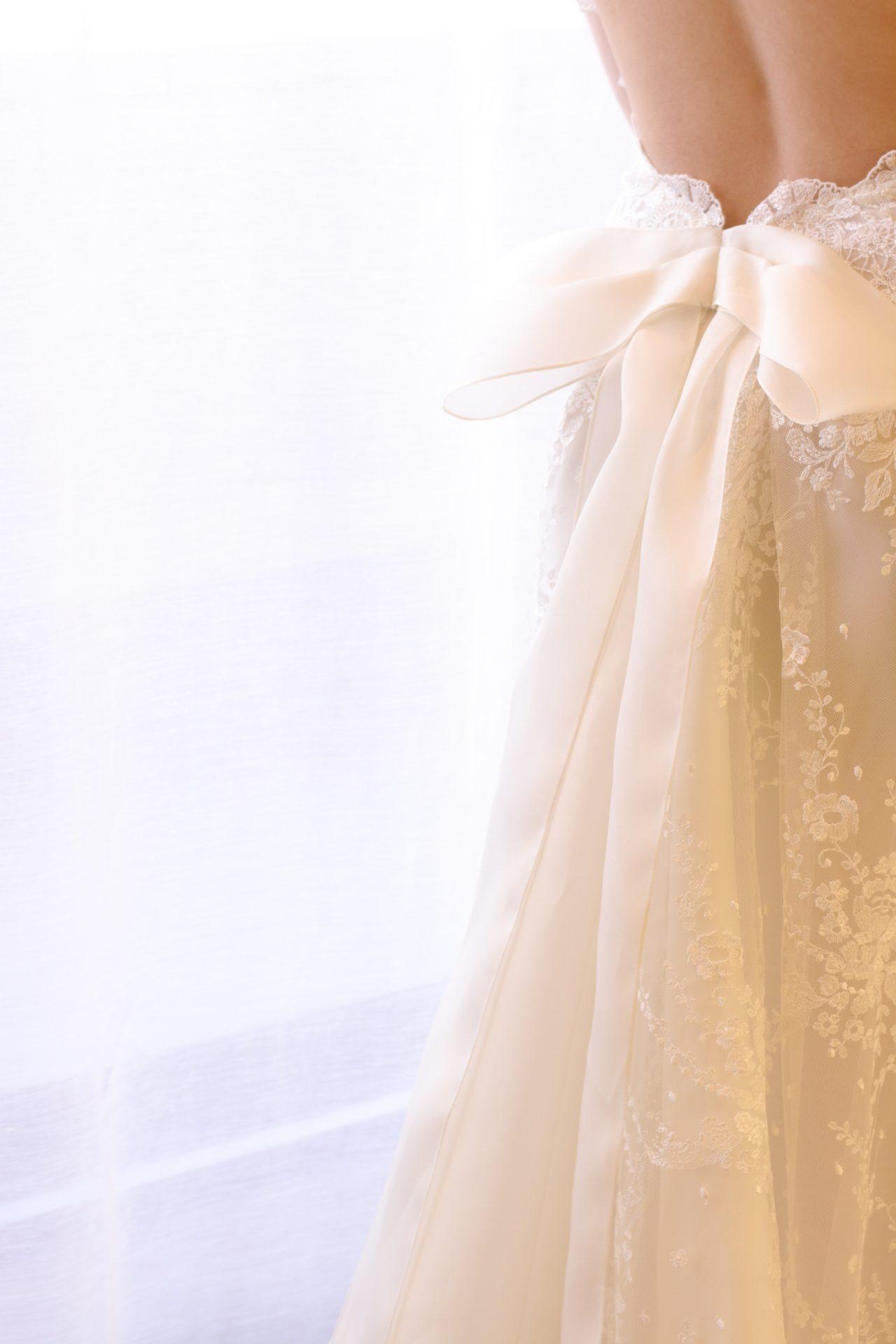 ヒップラインに添えられた立体的なビックリボンは、インポートドレスならではのシルクオーガンジーを使用しており、洗練された女性のフェミニンさを後ろ姿で表現しています
