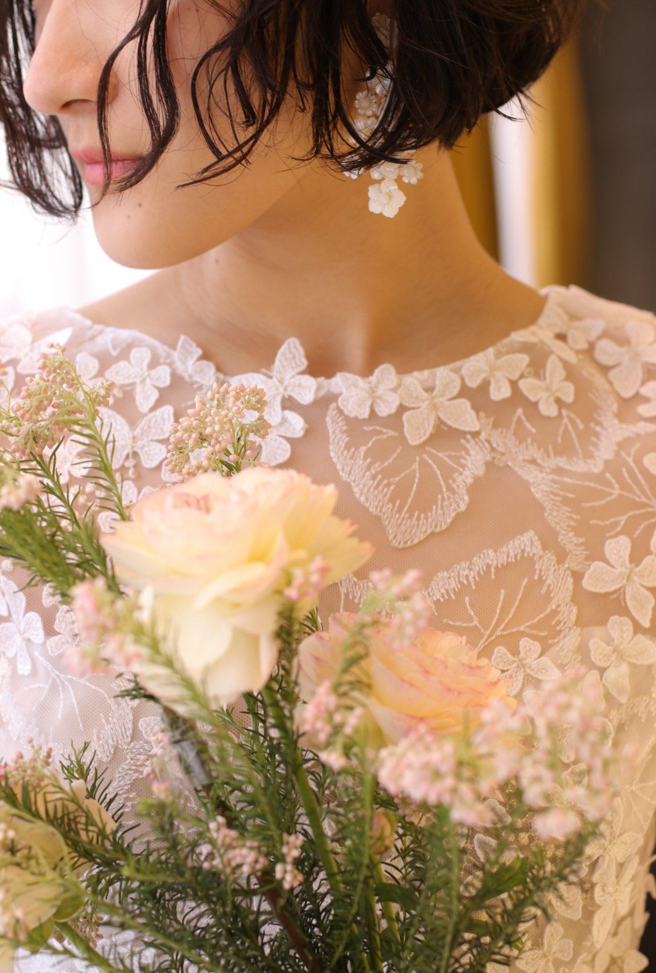 蝶々のレースのナチュラルな印象のドレスに薄いピンクのブーケを合わせれば、緑豊かなガーデンウェディングやアットホームなレストランウェディングにオススメの花嫁スタイルに