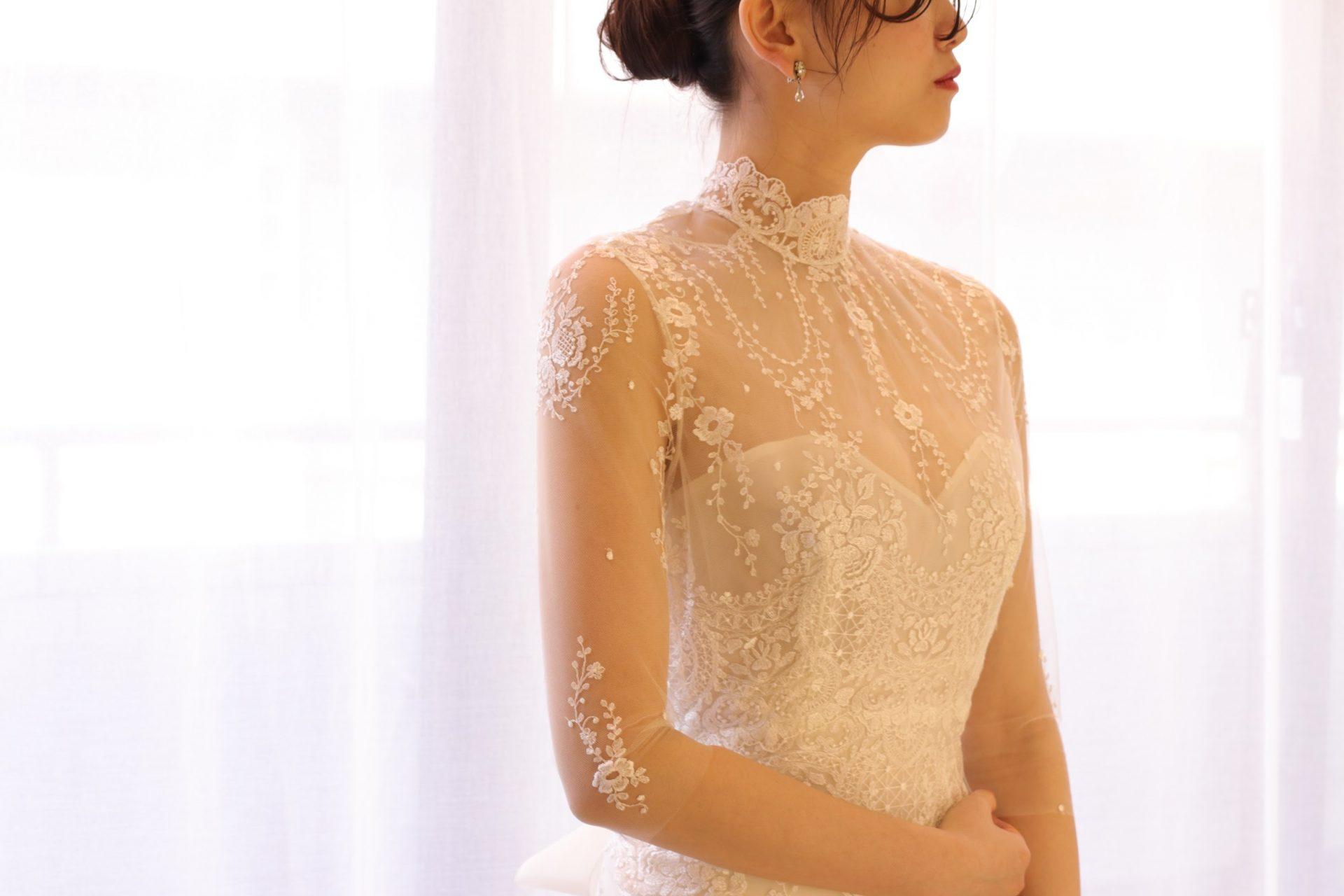 THETREATDRESSINGに届いたばかりのエリザベス・フィルモアのウェディングドレスは、ハイネックにロングスリーブというクラシカルな印象のデザインに、透明感と軽やかさを感じるレース使いで、上品な夏の結婚式にオススメの1着です