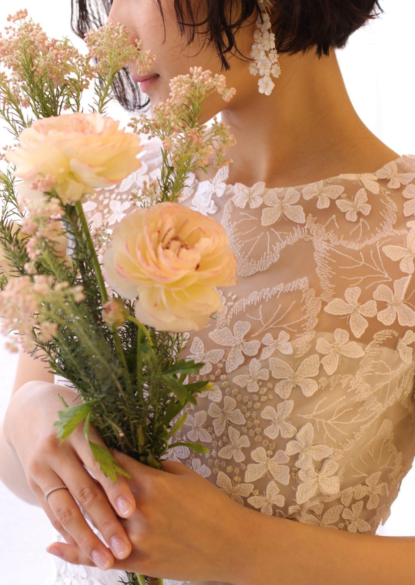 あじさいの花に蝶々が集まるようなレースをふんだんに使用したウェディングドレスに、ジャニファーベアの白い小花のイヤリングをコーディネートした、おしゃれなフェミニンスタイルです