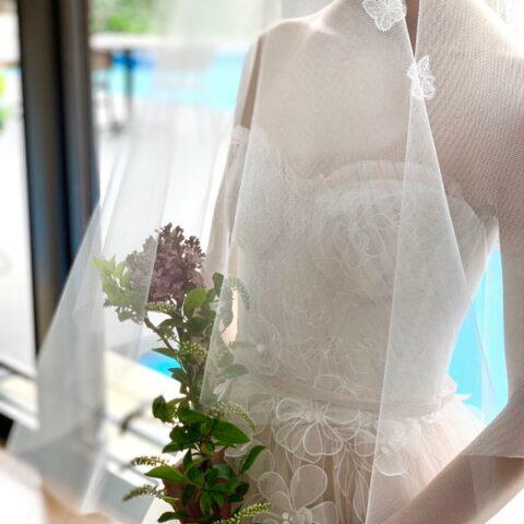 フラワーモチーフが繊細で女性らしいフェミニンなウエディングドレス
