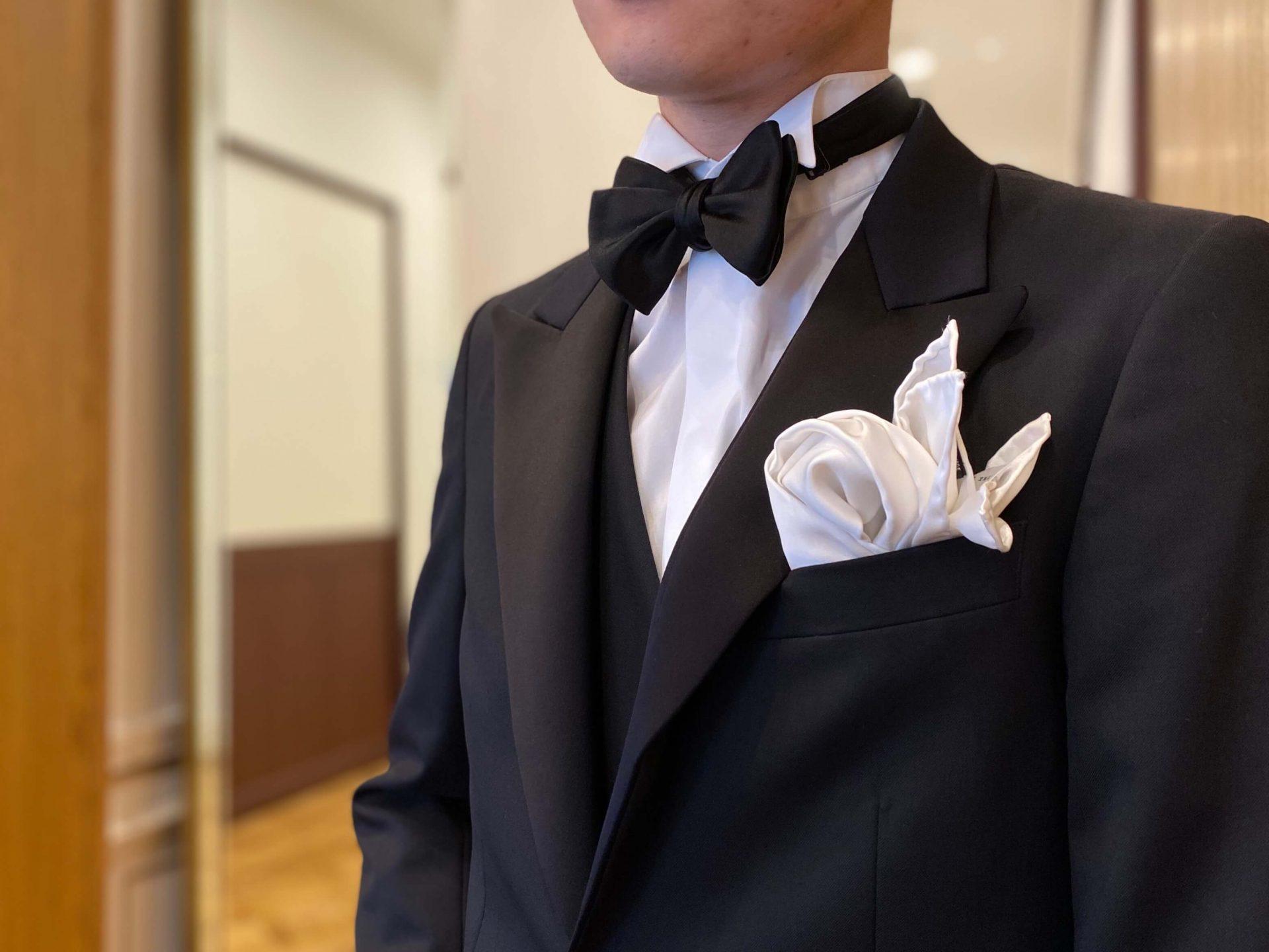 ブラックタイと光沢のあるチーフでまとめた新郎様のフォーマルスタイル