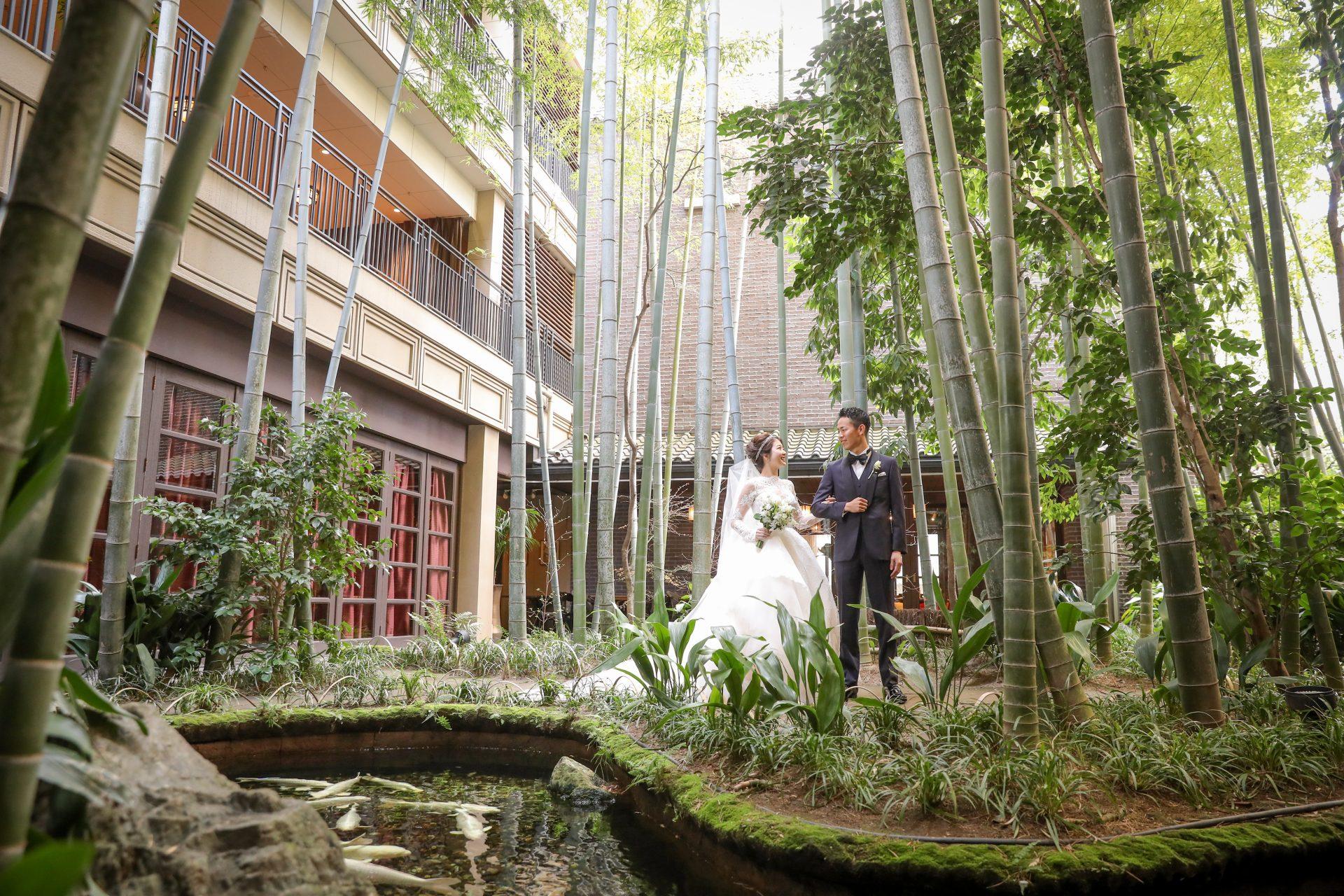 レースが美しくボリューム溢れるウエディングドレスとネイビーのタキシードをフォーチュンガーデン京都の竹林の前でお召しになられている新郎新婦様