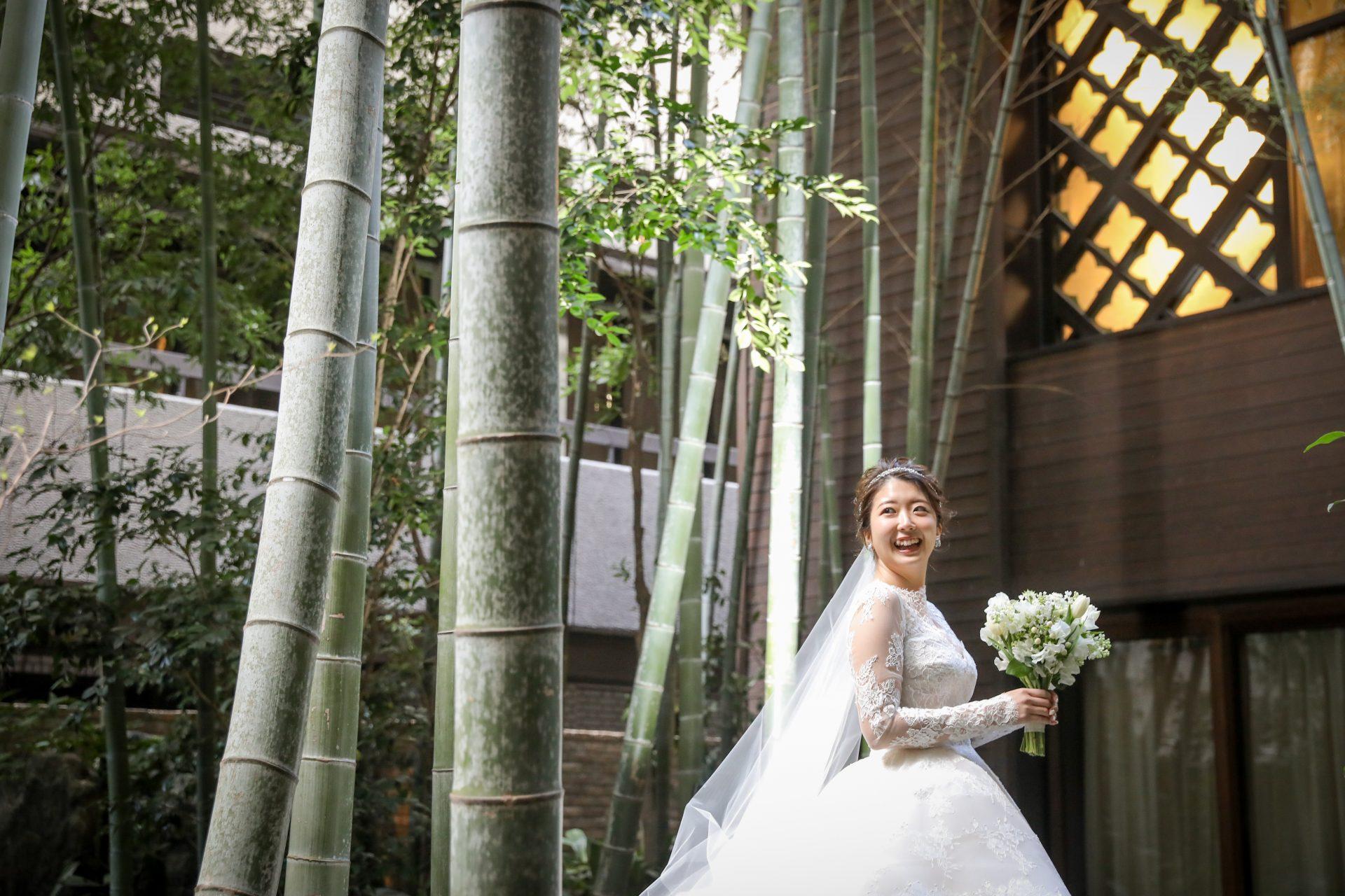 自然の中でロングベールに包まれるレースが美しくクラシックなモニークルイリエのウェディングドレスのご新婦様