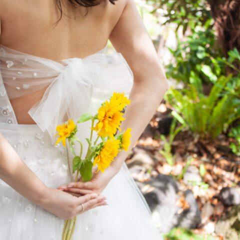 後ろ手にブーケを持つことで、ザ・トリート・ドレッシングオリジナルのバックリボンもしっかりお写真映えする、ザ・ルイガンズにぴったりのレンタルウェディングドレス