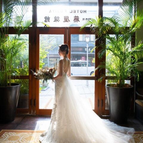 THE FUJIYA GOHONJINのエントランスでモニーク・ルイリエのスレンダーラインのウェディングドレスをお召しいただき前撮り撮影をしたご新婦様のバックショット