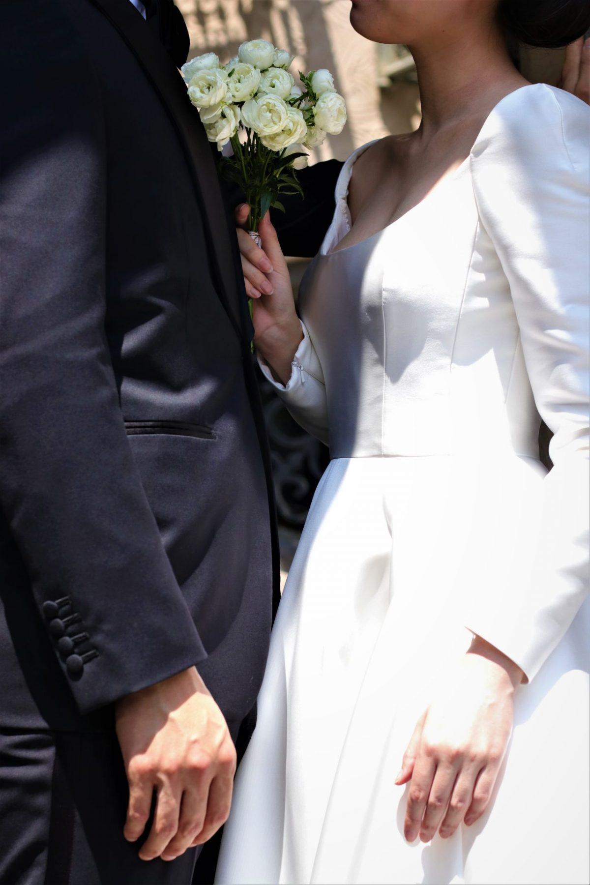 東京表参道のドレスショップTHETREATDRESSINGアディション店からご提案するのは、人気のシルクサテンのロングスリーブのウェディングドレスとフォーマルなブラックタキシードのコーディネートは秋冬の結婚式の新郎新婦様におすすめの組み合わせです