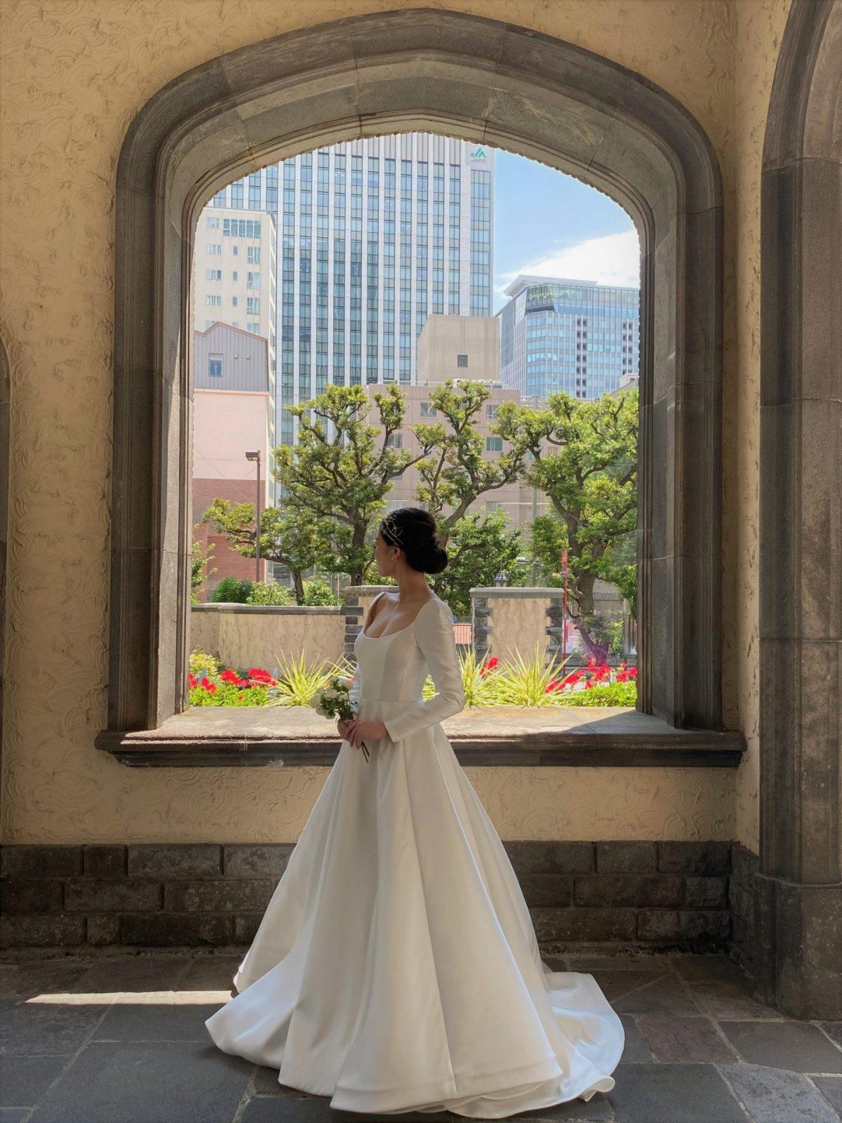 東京の都会の風景と有形文化財の赤坂プリンスクラシックハウスの趣ある建物に、ザ・トリート・ドレッシング アディション店のリームアクラの純白なウェディングドレスがとても映えます