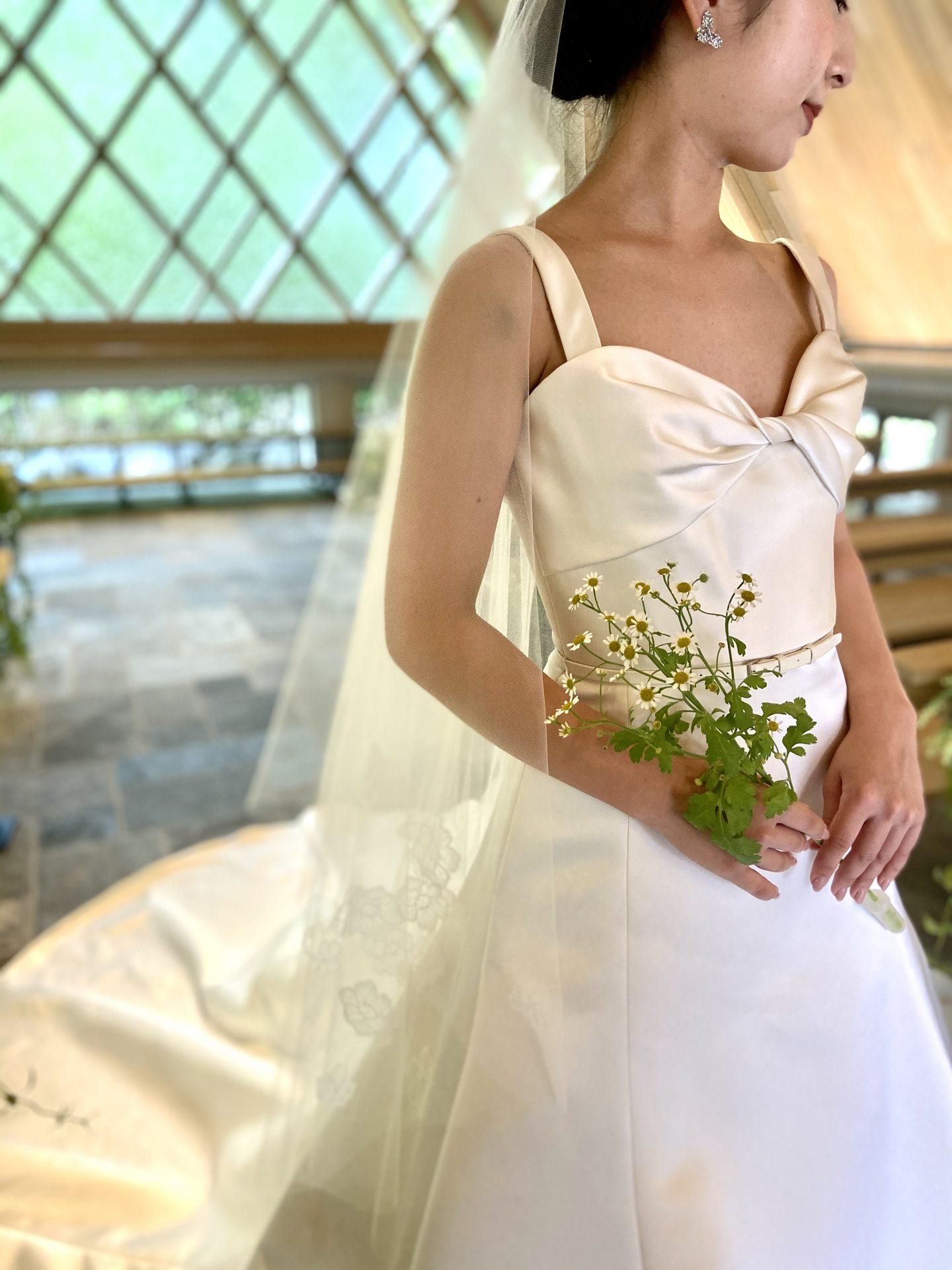 サテン生地のウェディングドレスに小花のブーケとフラワーモチーフのショートベールを合わせたナチュラルなコーディネート