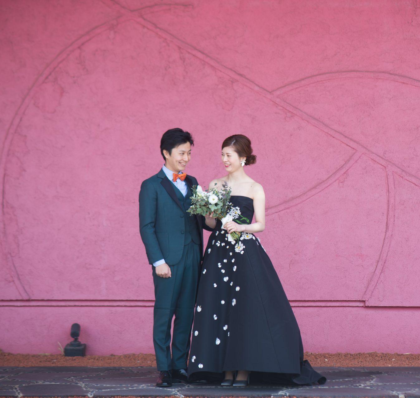 ザ・ルイガンズの赤い壁の前でおしゃれな前撮りが叶う、ザ・トリート・ドレッシングのカラードレス