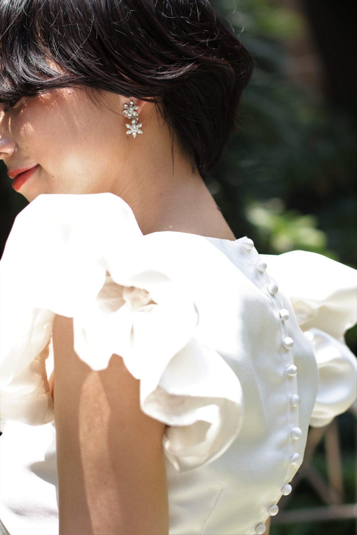 トレンドの肩付きのウェディングドレスは顔周りを華やかに見せるので、コーディネートはイヤリングやヘアスタイルはシンプルにまとめたり、ショートヘアの花嫁様にもお勧めです