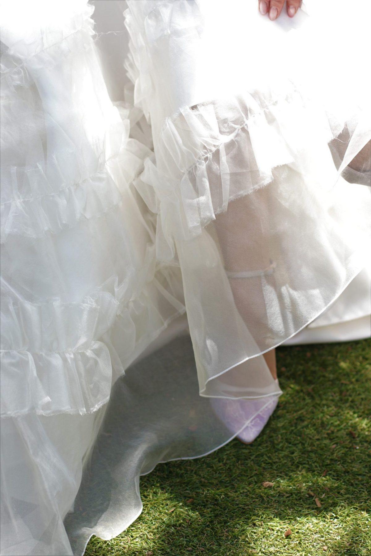 太陽の日差しが差し込むガーデン挙式の花嫁様に、ザ・トリート・ドレッシングのドレスコーディネーターが提案するのは、軽やかなオーガンジー素材のAラインのウェディングドレスにレース素材のブライダルシューズを合わせたコーディネートです