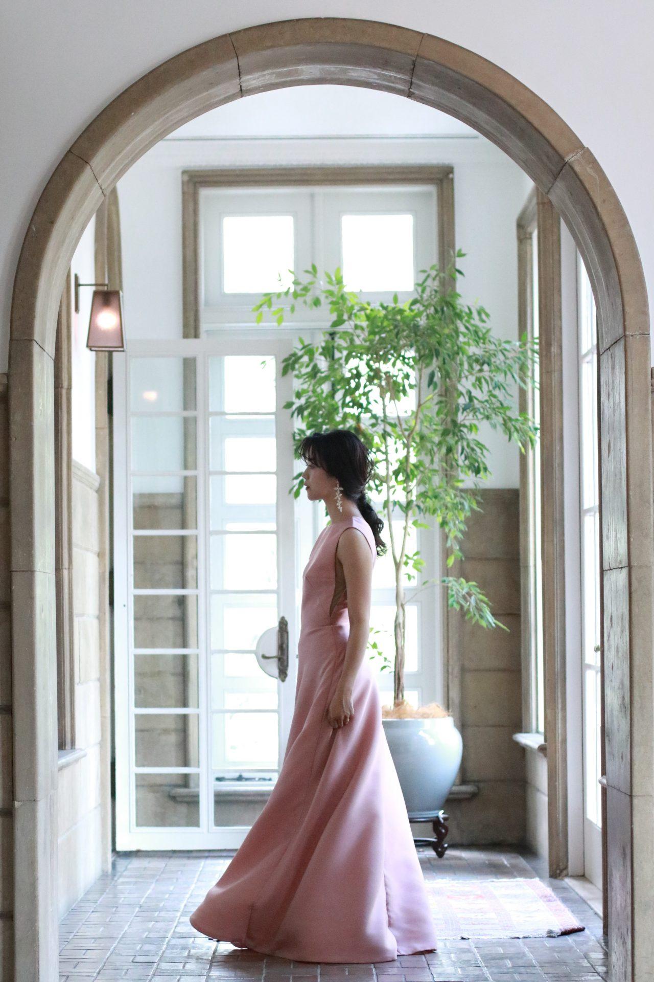 THETREATDRESSINGアディション店の提携会場である赤坂プリンスクラシックハウスの趣のあるチャペルや披露宴会場でも圧倒的な存在感を放つのは、自然な広がりが美しいAラインの大人なピンク色が素敵なカラードレスです