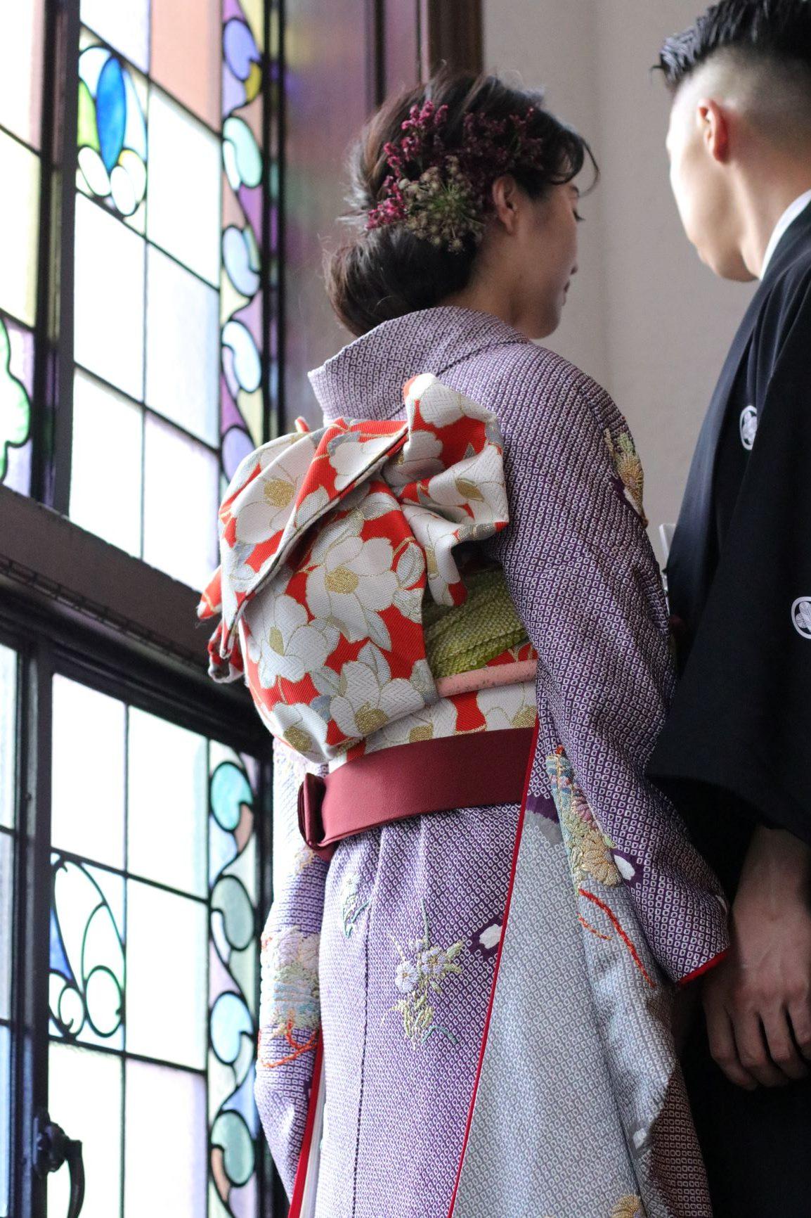 帯の結び方やお小物の合わせ方によって印象を変える本振袖は正面だけでなくバックスタイルも美しく、日本人女性らしい奥ゆかしく上品な印象中に花嫁様らしさを取り入れたコーディネートで、お写真を残していただくのはいかがでしょうか