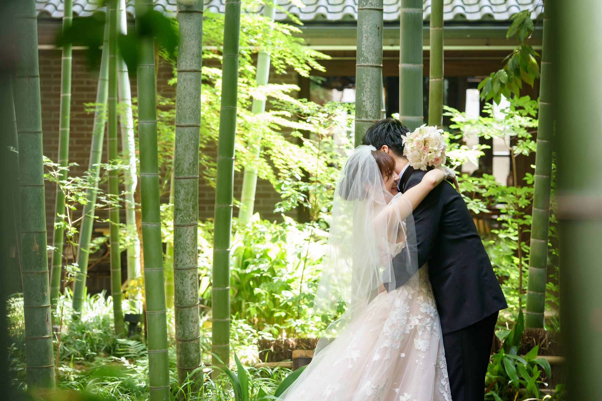 フォーチュンガーデン京都の竹林の前でボリュームあるAラインの大柄のレースが華やかなウエディングドレスをお召しになられた新婦様とブラックのタキシードをお召しになられた新郎様