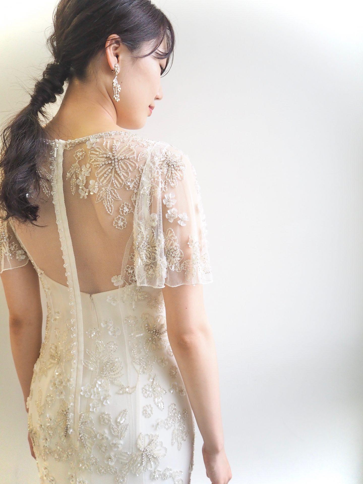 立体感のあるビーズがゲストの目を引く細身のウェディングドレスにラフなローポニーでまとめた大ぶりなイヤリングを合わせたコーディネート。