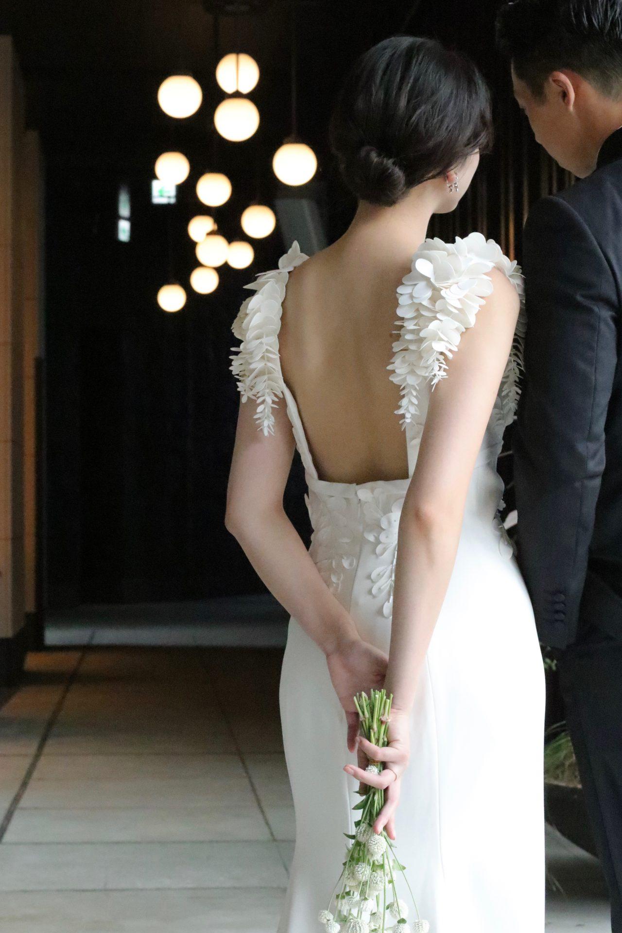 レストランウェディングやホテルウェディングにピッタリな大人な花嫁様にオススメしたいウェディングドレスは、とろみのあるクレープ素材のスレンダーラインに、背中が大きく空いたバックスタイルにショルダーには3Dフラワーのモチーフがデザインされたお洒落な1着です