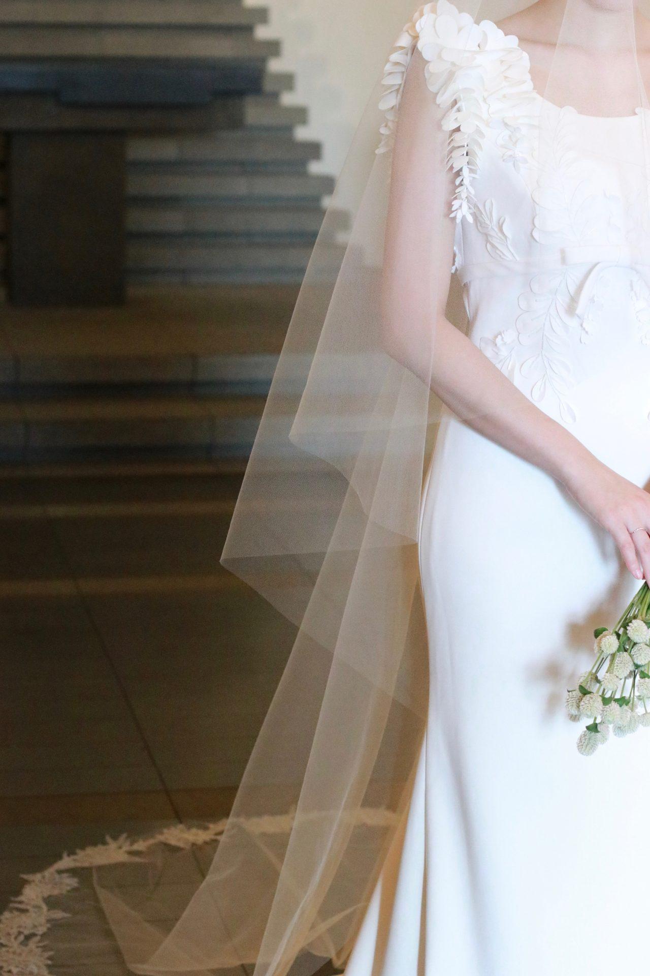 藤の花からインスピレーションを受けた3Dフラワーが施されたクレープ素材のウェディングドレスに、トリート・メゾンの繊細な刺繍が美しいロングベールを合わせたコーディネートは、暖かい日差しに包まれるような春の結婚式にオススメです