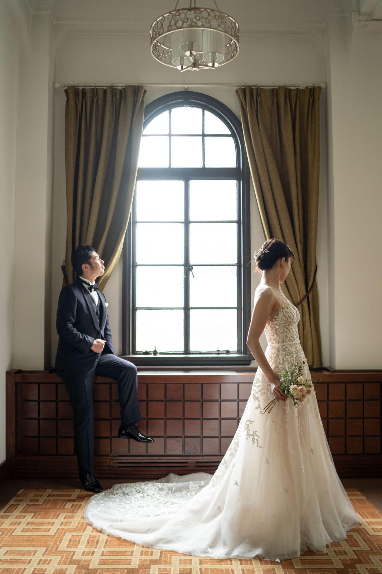 リーフ型の刺繍が贅沢にあしらわれたフォーチュンガーデン京都店おすすめのウエディングドレスとネイビーのタキシードのコーディネートで仕上げた新郎新婦様