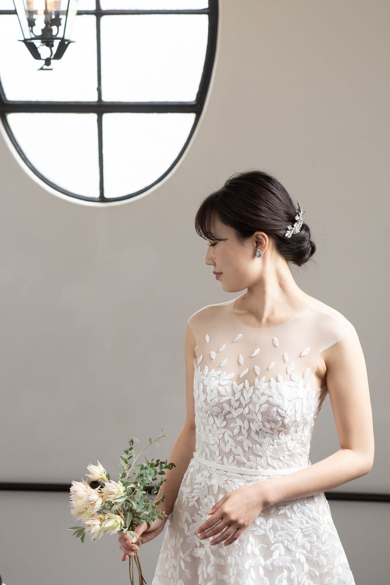 胸元に浮かぶように施されたリーフのモチーフが美しいウェディングドレスには輝きのあるヘッドパーツと小ぶりのイヤリングを合わせナチュラルですっきりとしたコーディネートがおすすめ