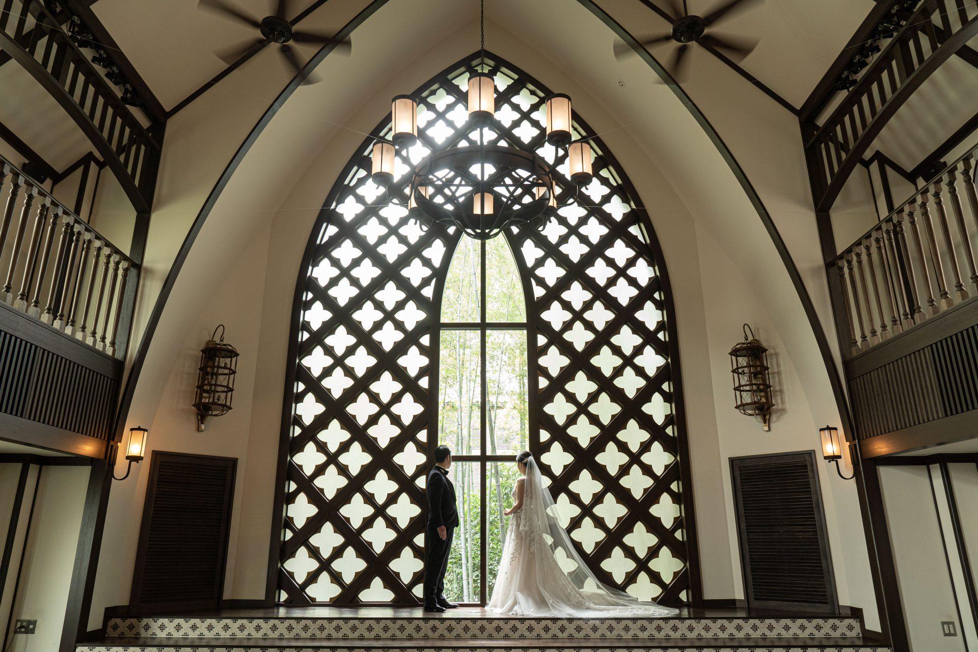 七宝柄のウィンドウが印象的で大聖堂のようなフォーチュンガーデン京都のチャペルで透明感溢れるロングトレーンのウェディングドレスをお召しになる新婦様とタキシード姿のご新郎様