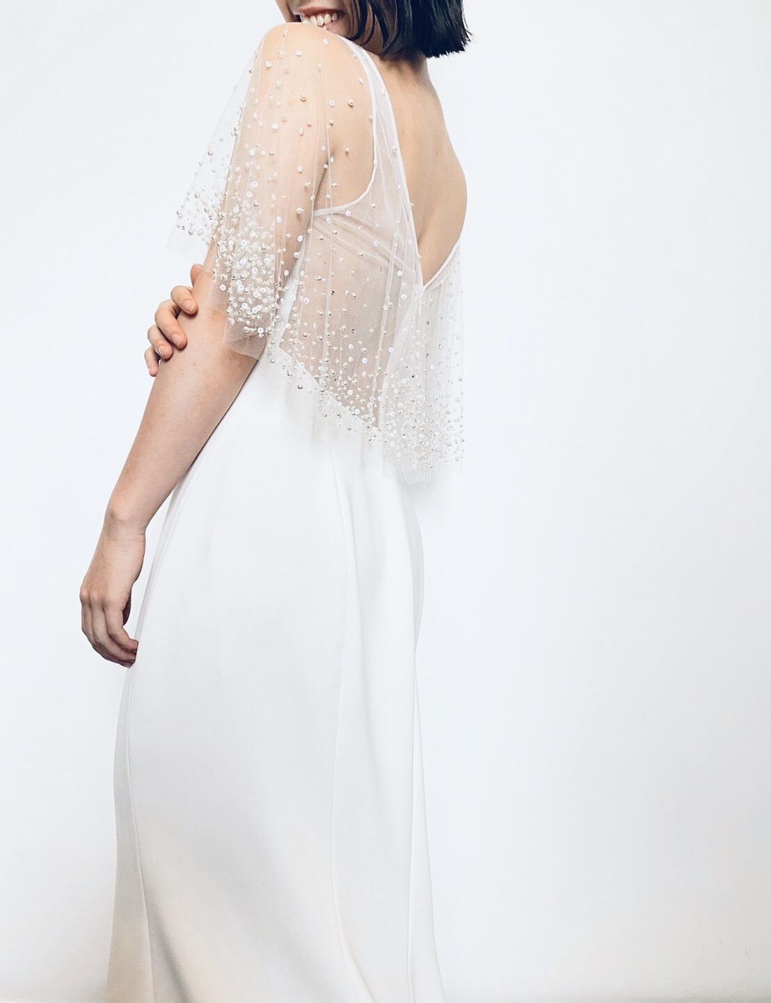 プレ花嫁におすすめしたい華やかなビーディングが施されたケープのデザインのマーメイドラインのウェディングドレス