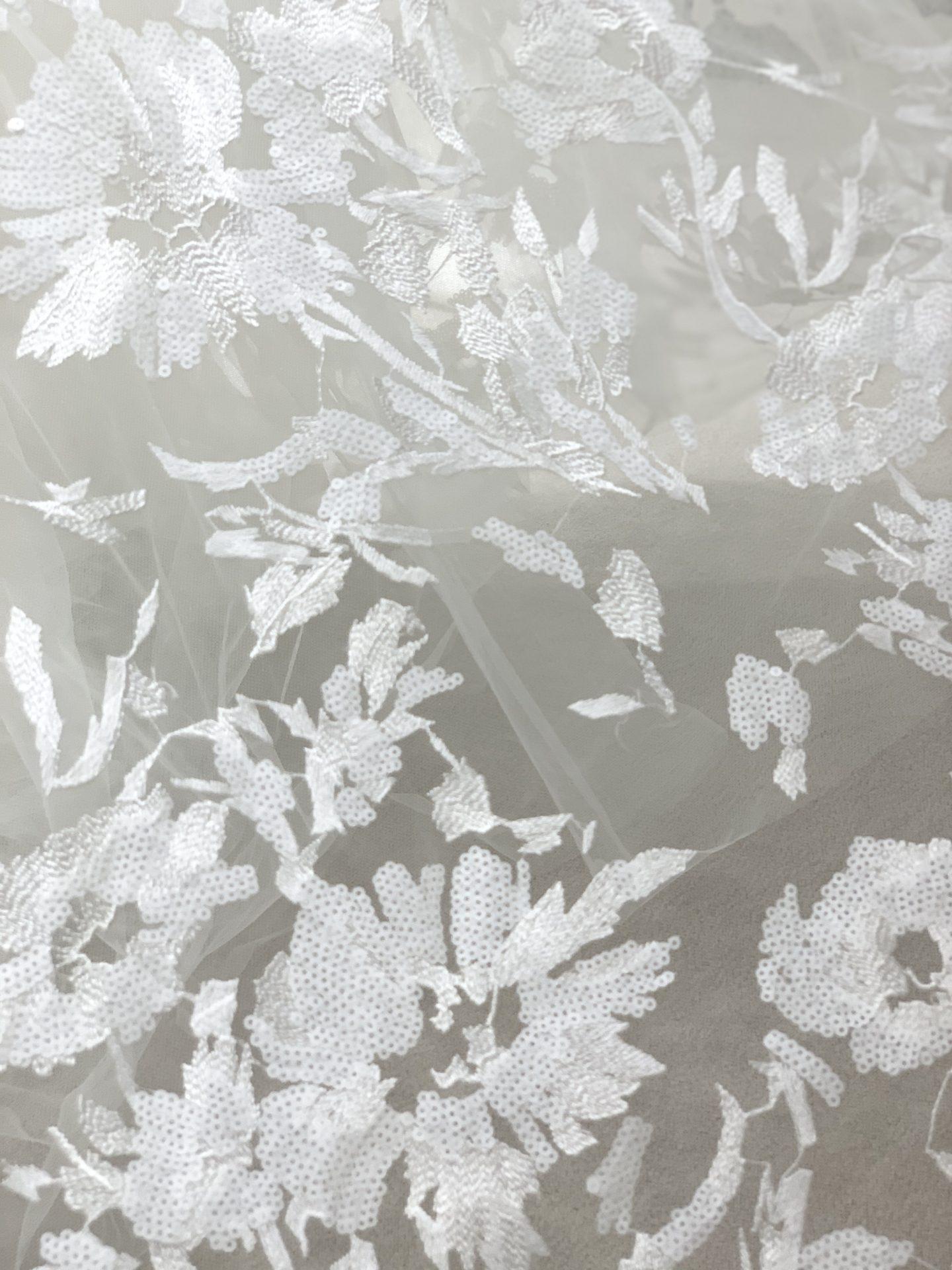 立体的なコードリバーレースや繊細なシャンテリーレースが施された美しいAラインのウェディングドレス