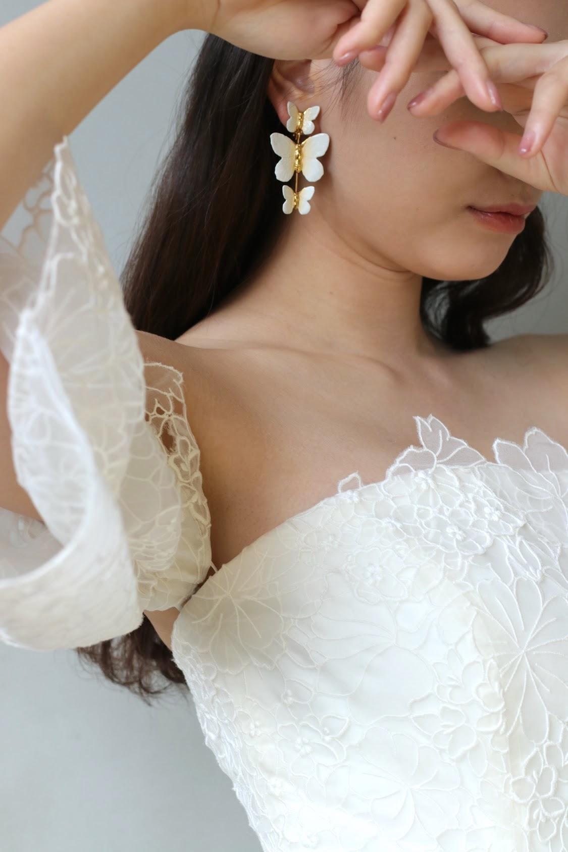 春夏の結婚式におすすめの最旬トレンドのロマンティックなドレスにはピンクのリップとネイル、蝶モチーフの白やゴールドのイヤリングを合わせると、幸福感溢れるいつまでも愛されるトータルコーディネートでありながらもフルダウンヘアにする事でモードな花嫁になることができます。