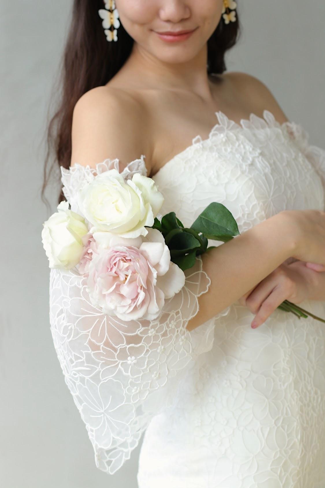 パレスホテル東京などの一流ホテルでの結婚式に人気のブランド キャロリーナ・ヘレラの新作のウェディングドレスは、トレンドの取り外しできるベルスリーブのデザインなので、二の腕が細く見える効果があり、ブーケを抱えた仕草が可憐で華やかになります