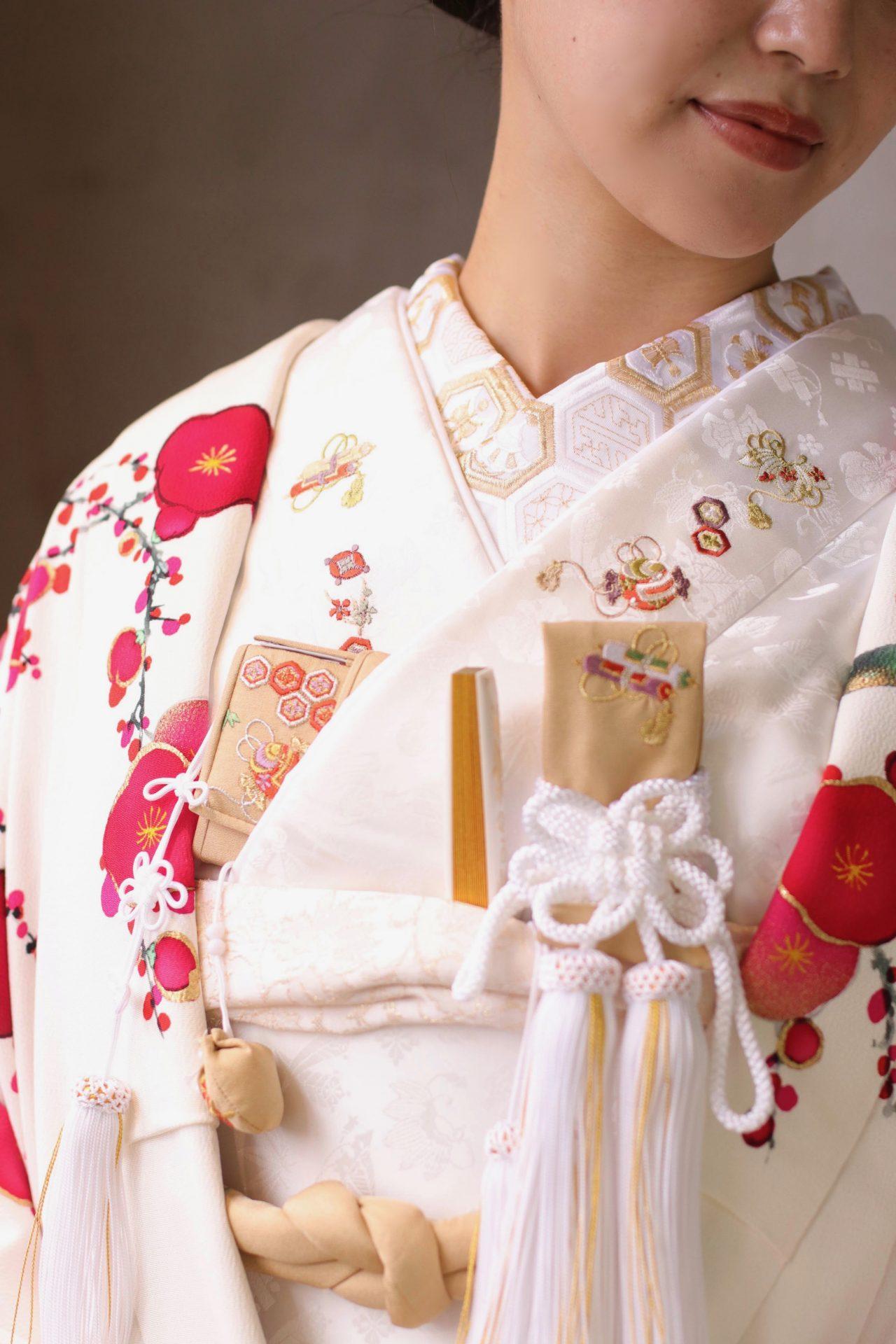 赤坂プリンスクラシックハウスの花嫁様におすすめしたいのは、繁栄を意味する亀甲文様の半襟と、福徳を呼ぶ宝尽くしの刺繍の掛下に、ベージュの和装小物を合わせた白打掛のコーディネートです