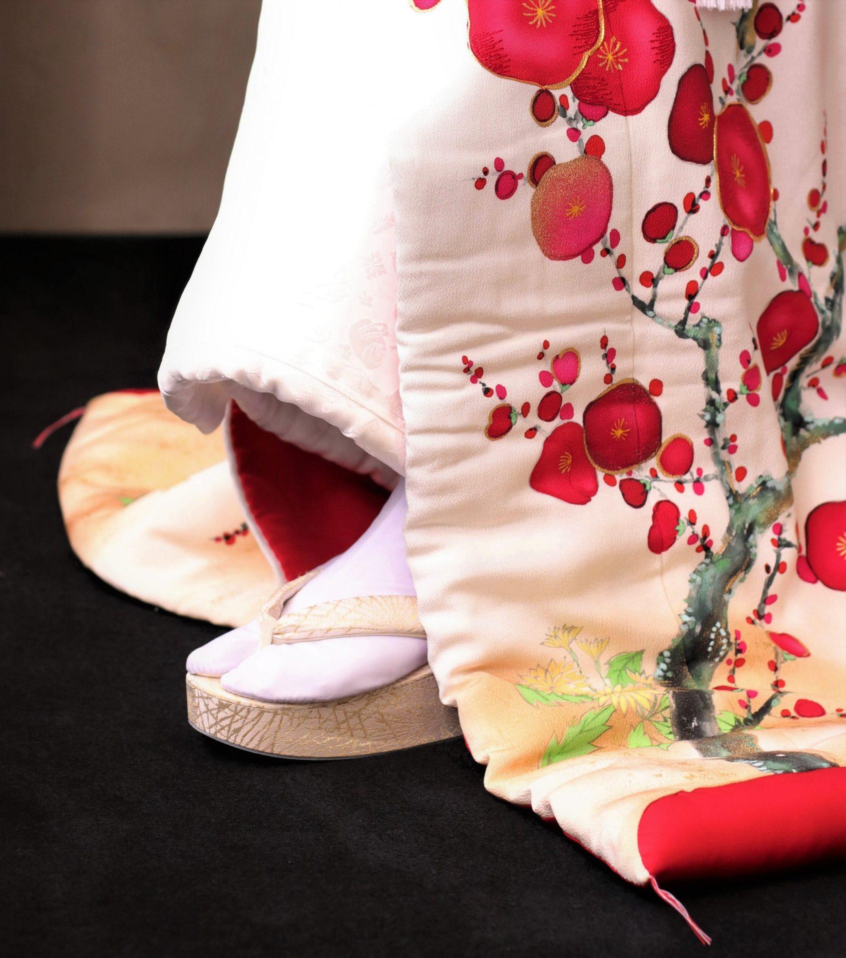 暖かい日差しの中で執り行う春の結婚式にピッタリな紅白の彩り美しい紅梅柄の色打掛に、金色の草履を合わせることで可愛らしい雰囲気の中にも大人っぽい印象がある大人可愛い花嫁姿に仕上がります