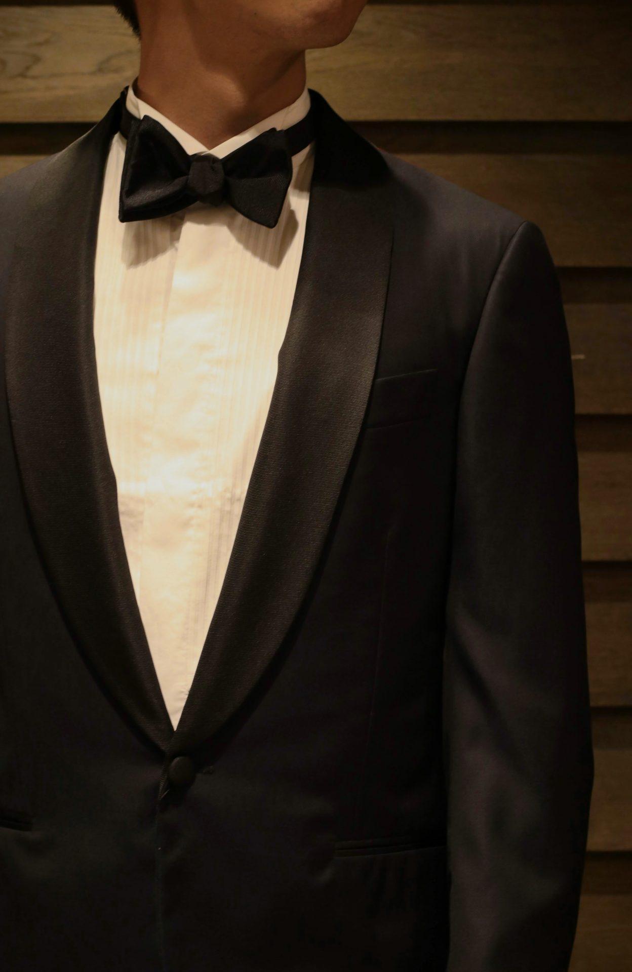 タキシードにブラックの蝶ネクタイとプリーツシャツを合わせた正統なフォーマルスタイルを表参道にあるTHE TREAT DRESSING ADDITION店(ザ・トリート・ドレッシング アディション店)がご紹介します。提携するパレスホテル東京などの格式高い結婚式会場にお勧めのスタイルです。