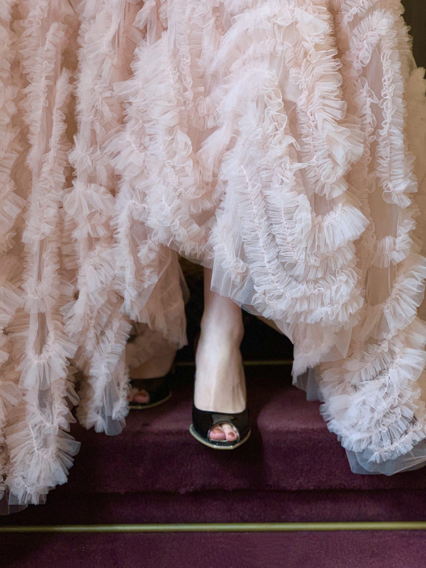 THE TREAT DRESSING(ザ・トリート・ドレッシング)のピンクのカラードレスの裾元からブラックのオープントゥのシューズをのぞかせるおしゃれなお色直しのコーディネート