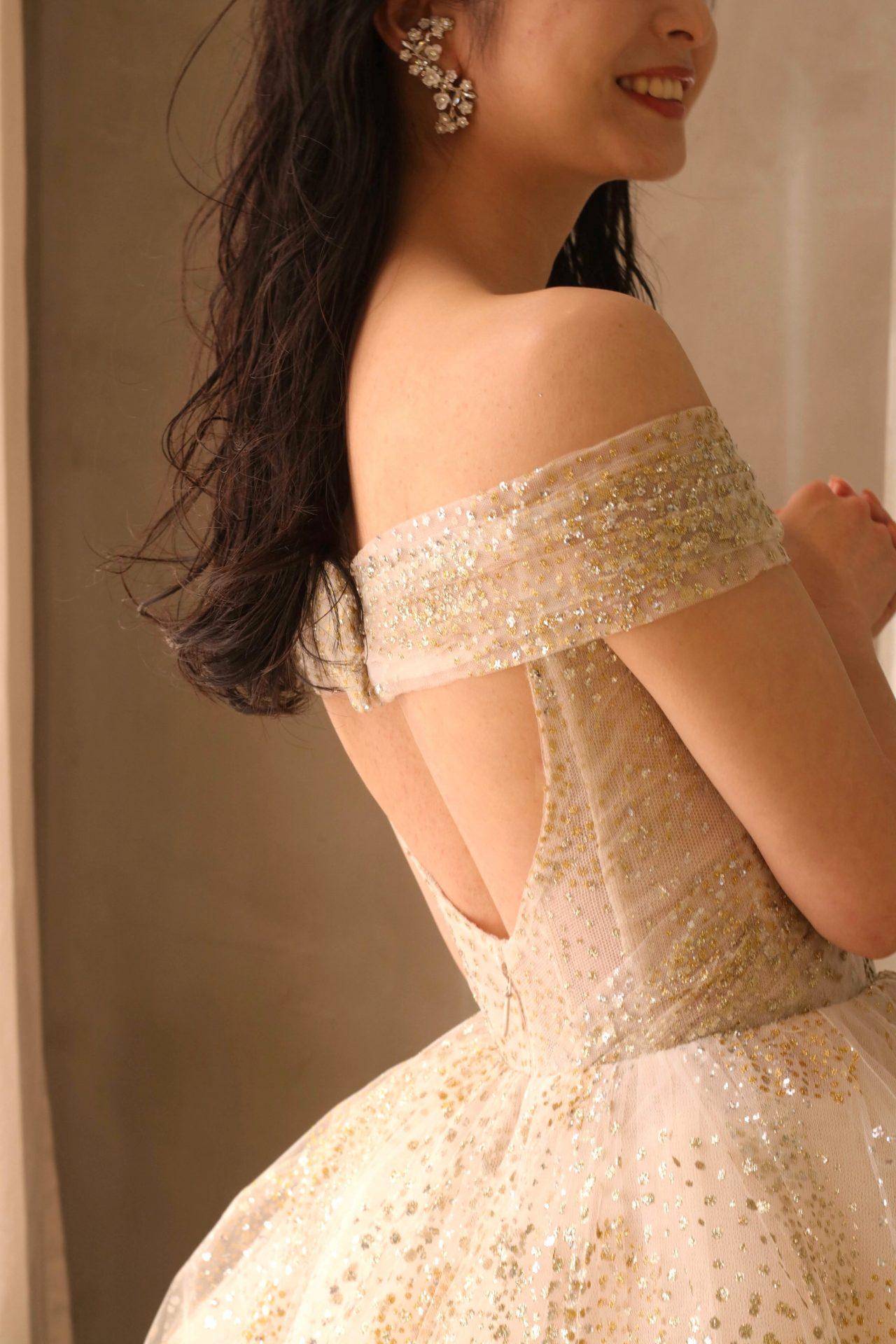 後ろ姿に視線を集める、背中の空いたバックコンシャスなお色直しのカラードレスにおすすめのコーディネートはダウンスタイルで大ぶりのフラワーモチーフのイヤリングを合わせた大人ナチュラルな雰囲気です