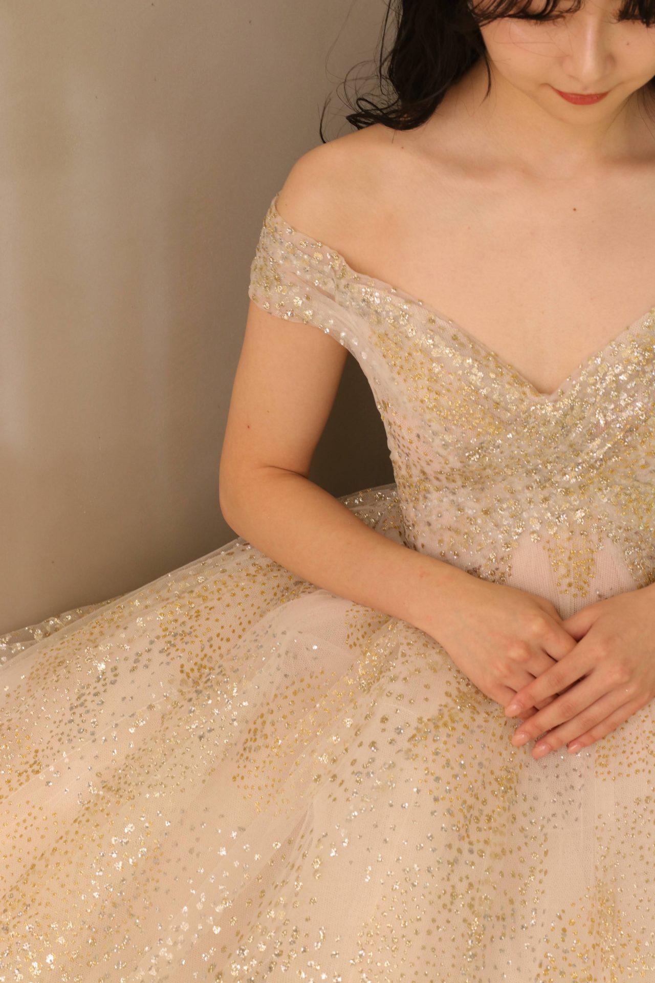 ゴールドとシルバーのグリッターが華やかなプリンセスラインのカラードレスはデコルテラインを美しく見せてくれるオフショルダーのデザインで赤坂プリンスクラシックハウスなどのクラッシックな会場にも映える洗練された花嫁様にもおすすめです
