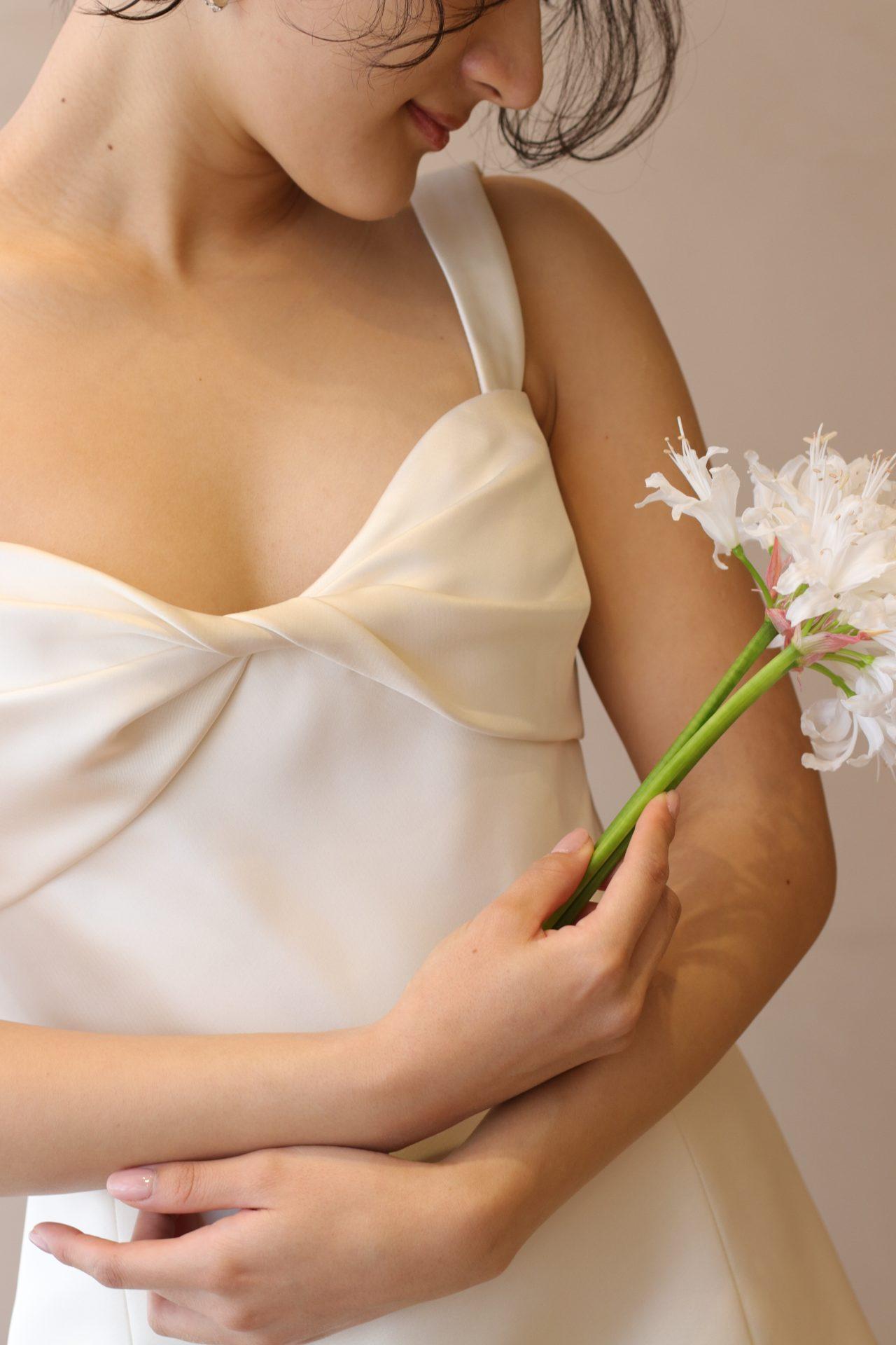 上質なシルク生地のシンプルなウェディングドレスに合わせた白い小花を散らした優しい印象のブーケは、春夏のガーデンウェディングやレストランウェディングなどの、親族や友人のみで行うアットホームな式をイメージされている花嫁様におすすめです