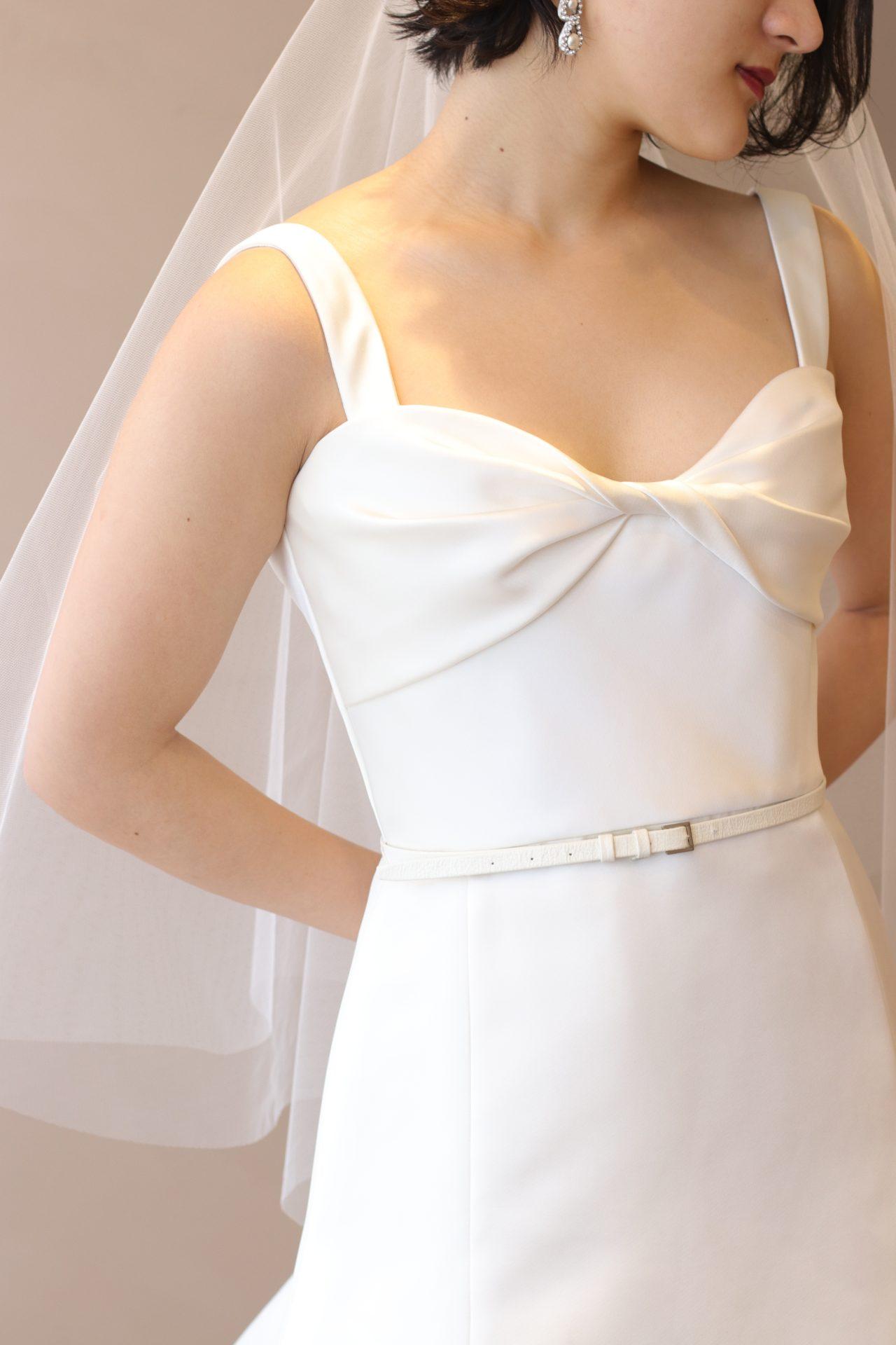 世界中の花嫁から人気のあるエリー・サーブブライドの新作ウェディングドレスは、シンプルでありながらも胸元にアイキャッチーなリボンモチーフが施された唯一無二なデザインがゲストの目を引く30代の大人の女性に人気の1着です