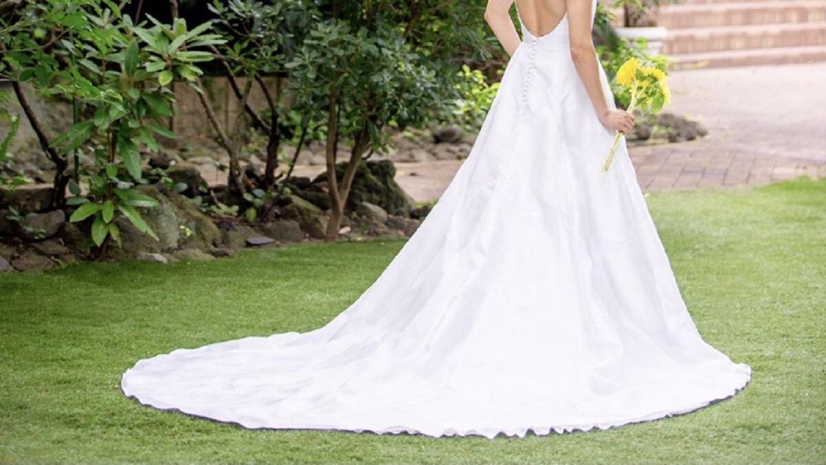 弧を描くなめらかなバックトレーンが印象的な、ガーデンウエディングに人気なAラインウエディングドレス