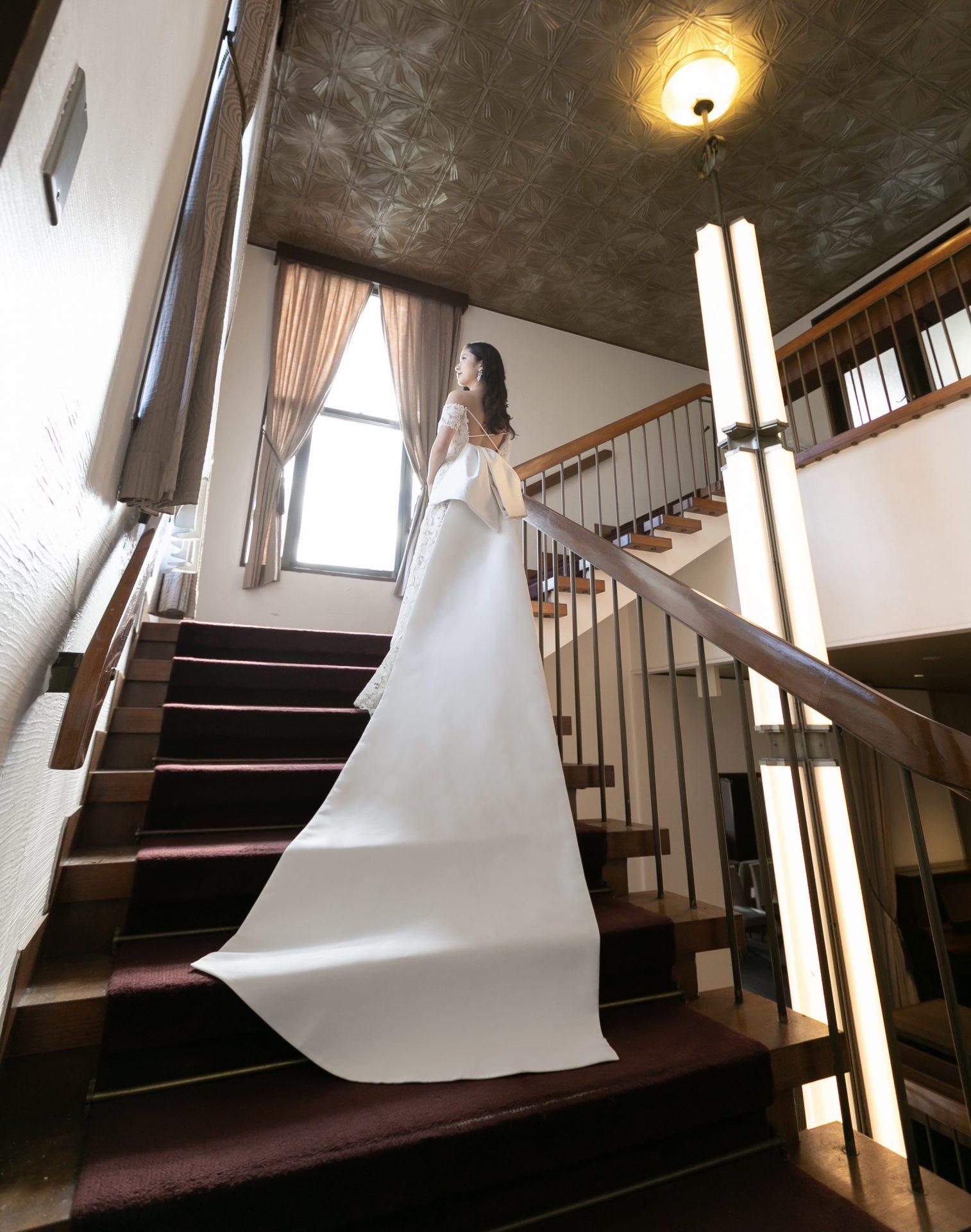 クラシックでエレガントな螺旋階段に映えるトレーンの長いクラシカルなウェディングドレス