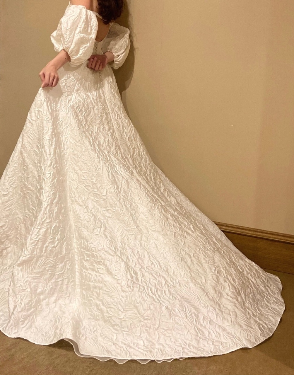 フラワーモチーフのジャガード素材が愛らしく、柔らかでふんわりとしたボリュームのあるウエディングドレス