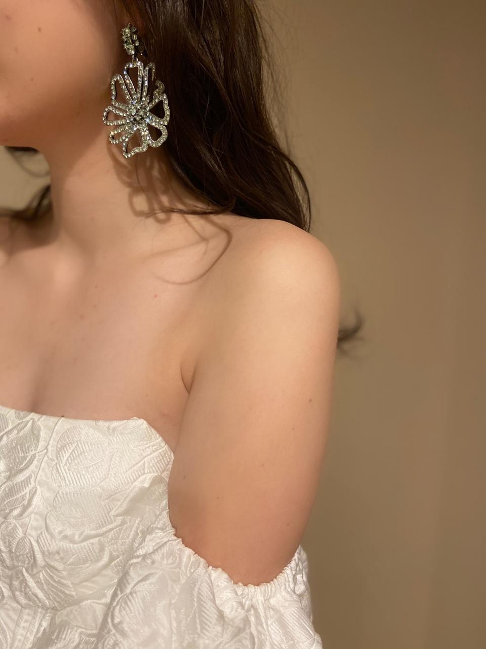 クリアブルーの大振りなフラワーモチーフのイヤリングを合わせ、モダンなドレスをよりファッショナブルな印象に