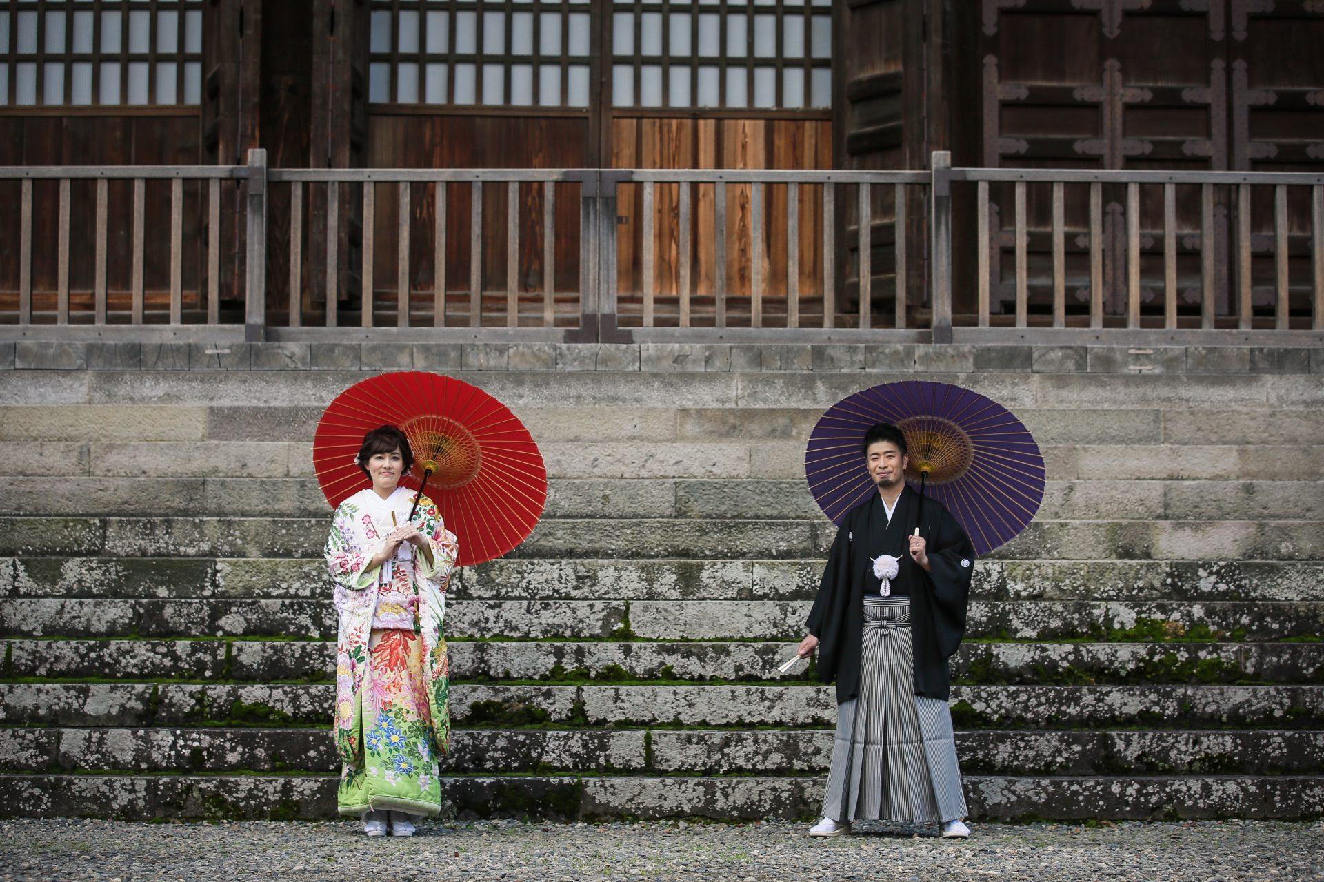 善光寺本堂前で鮮やかな赤と高貴な紫の番傘を持ちながら長野らしい前撮りを楽しまれたご新郎ご新婦様