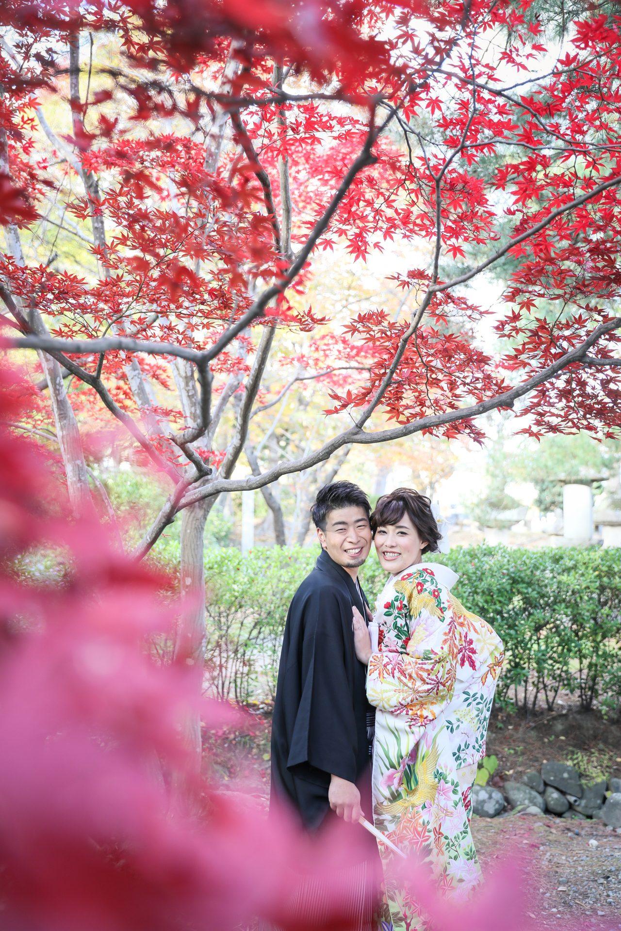 目が覚めるような赤い紅葉の中で寄り添う和装がお似合いのご新郎ご新婦様