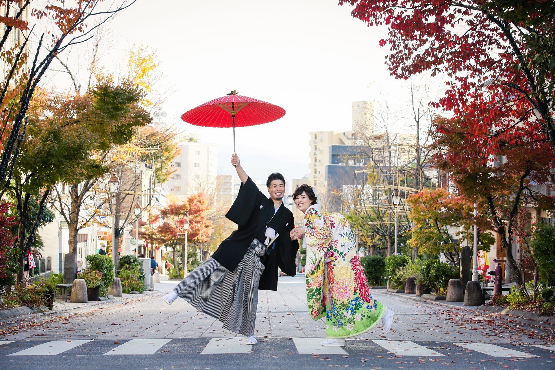 善光寺から長野駅まで一直線に続く門前通りで紅葉に映える染めの色打掛と格式高い黒紋付をお召しになりお二人らしい楽しげなショットを撮影されたご新郎ご新婦様