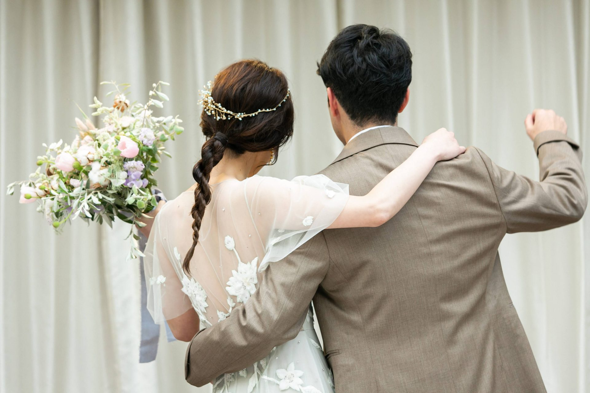 バックコンシャスなパステルグリーンのカラードレスに合わせてベージュのタキシードを選ばれたリストランテASOで結婚式を挙げたご新郎様ご新婦様。