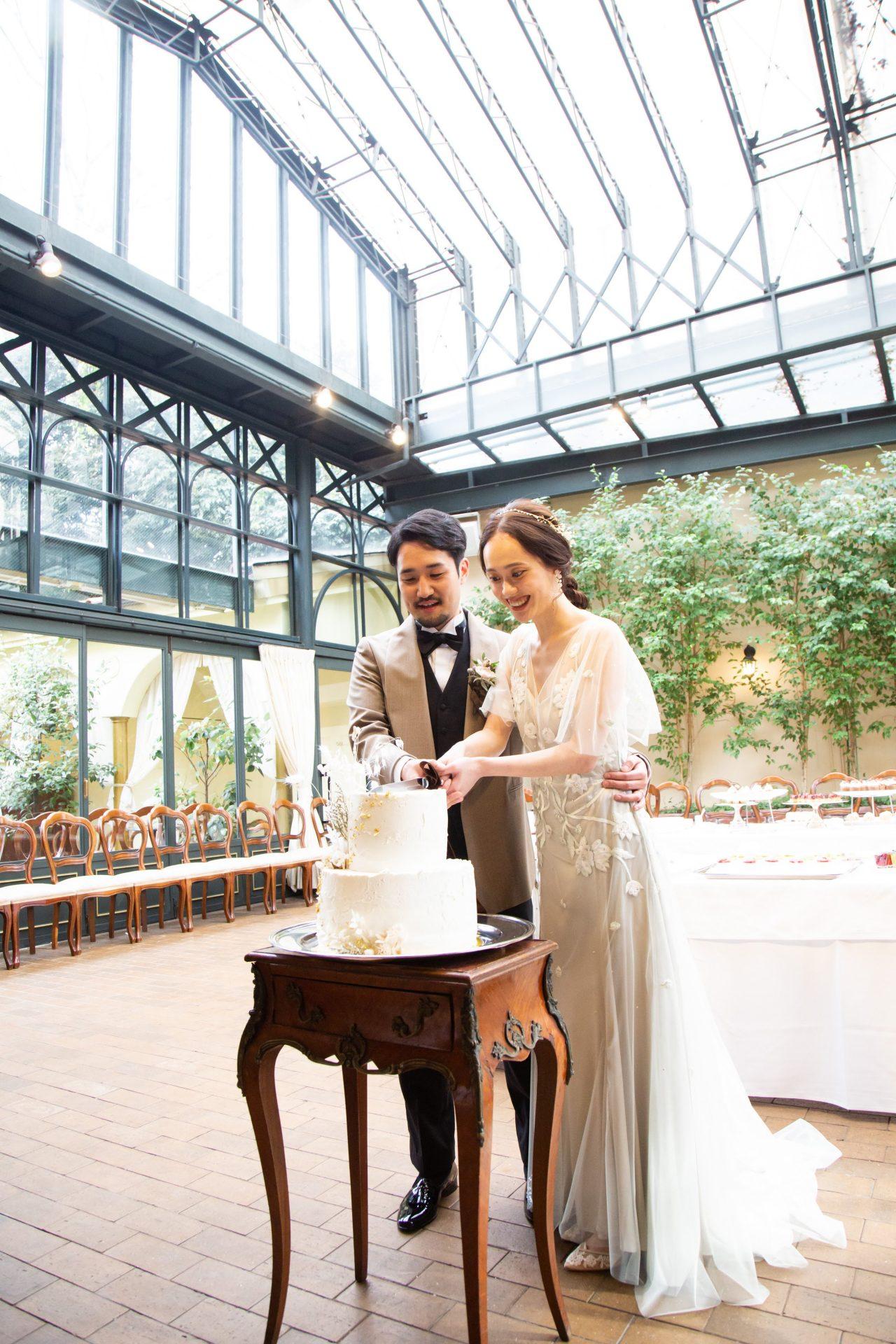 自然光が降り注ぐ開放感溢れるチャペルの中で、インポートブランド アレクサンドラ・グレッコのカラードレス姿で行ったケーキ入刀の様子です
