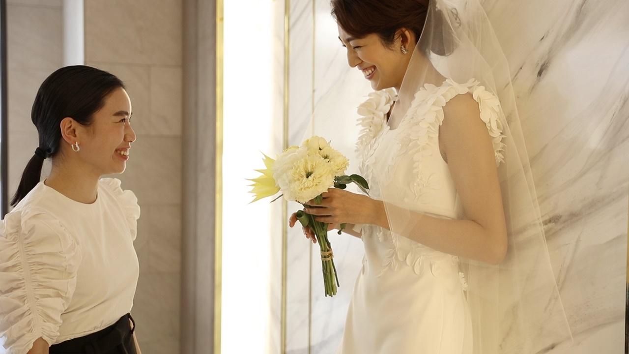 3Dの藤の花がついたヴィクター&ロルフ・マリアージュのウェディングドレスを身に纏った望月芹名さんに語りかけるPR飯島