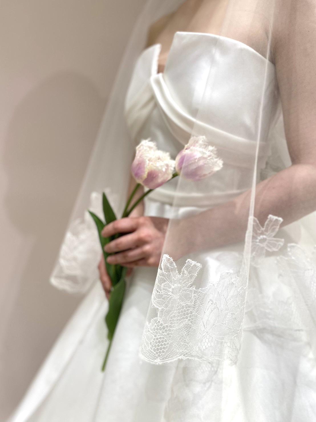 """""""シンプルなウェディングドレスにトリート・ドレッシングオリジナルのチューリップ柄のベールを合わせたフェミニンなコーディネート<br"""